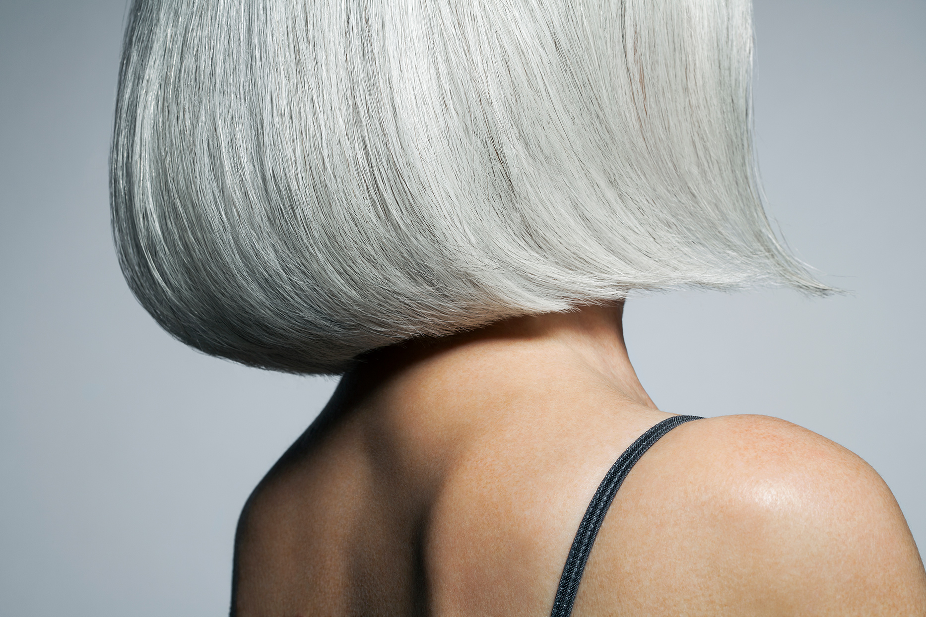 person wearing thin strapped top with bob cut thick gray hair
