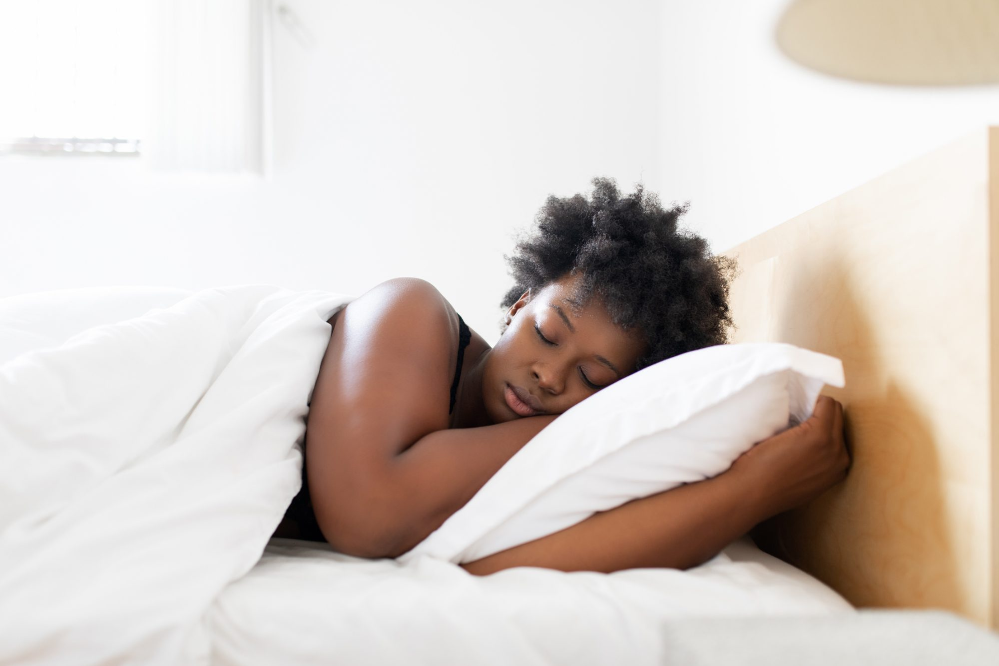 person sleeping in bed with white bedding