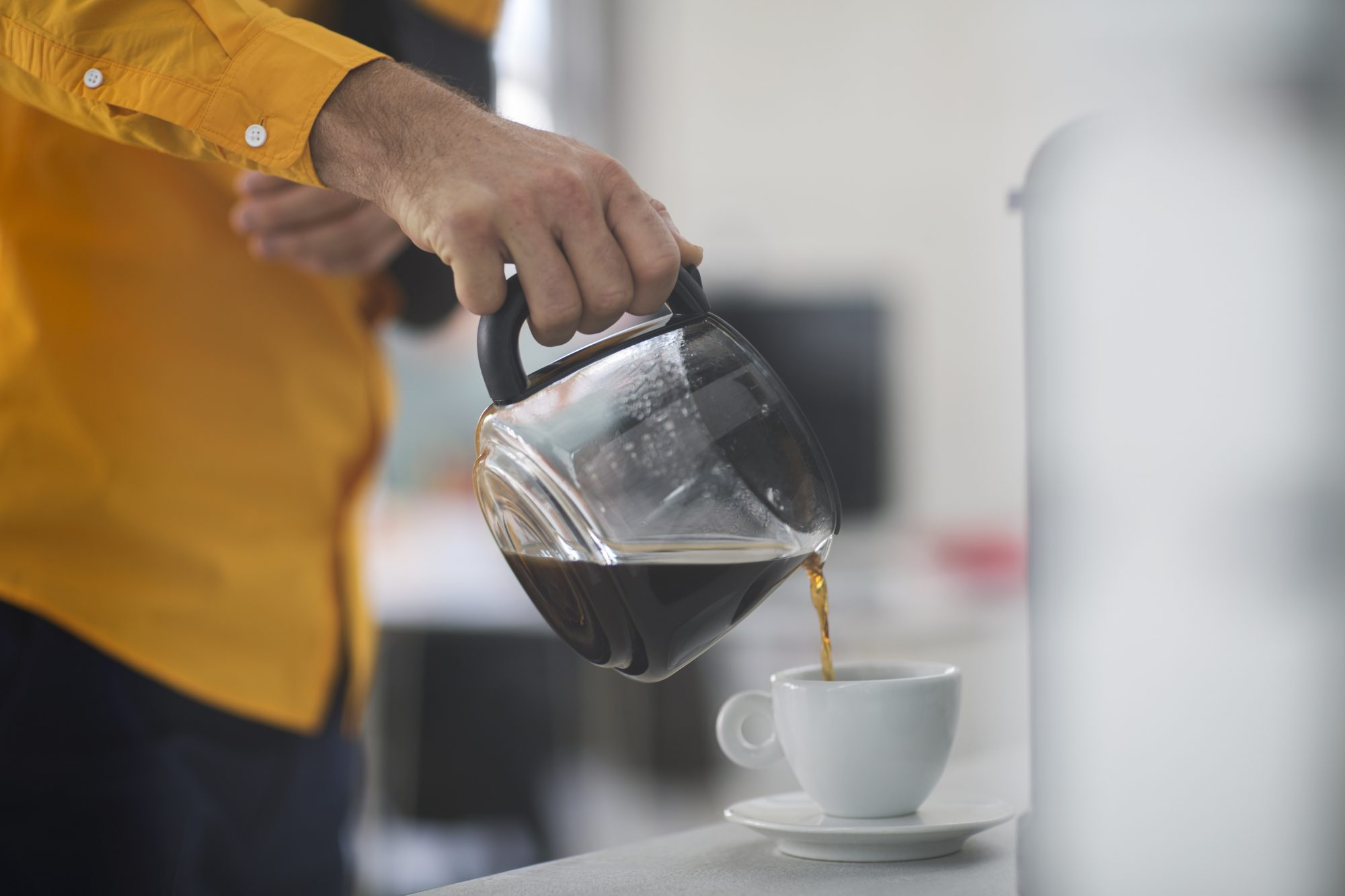 employee pouring coffee into cup