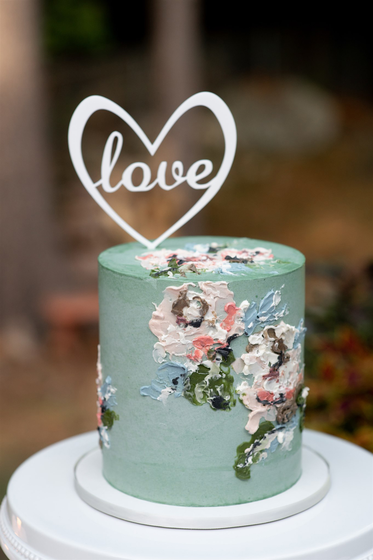 """Teal-colored wedding cake with """"love"""" topper"""