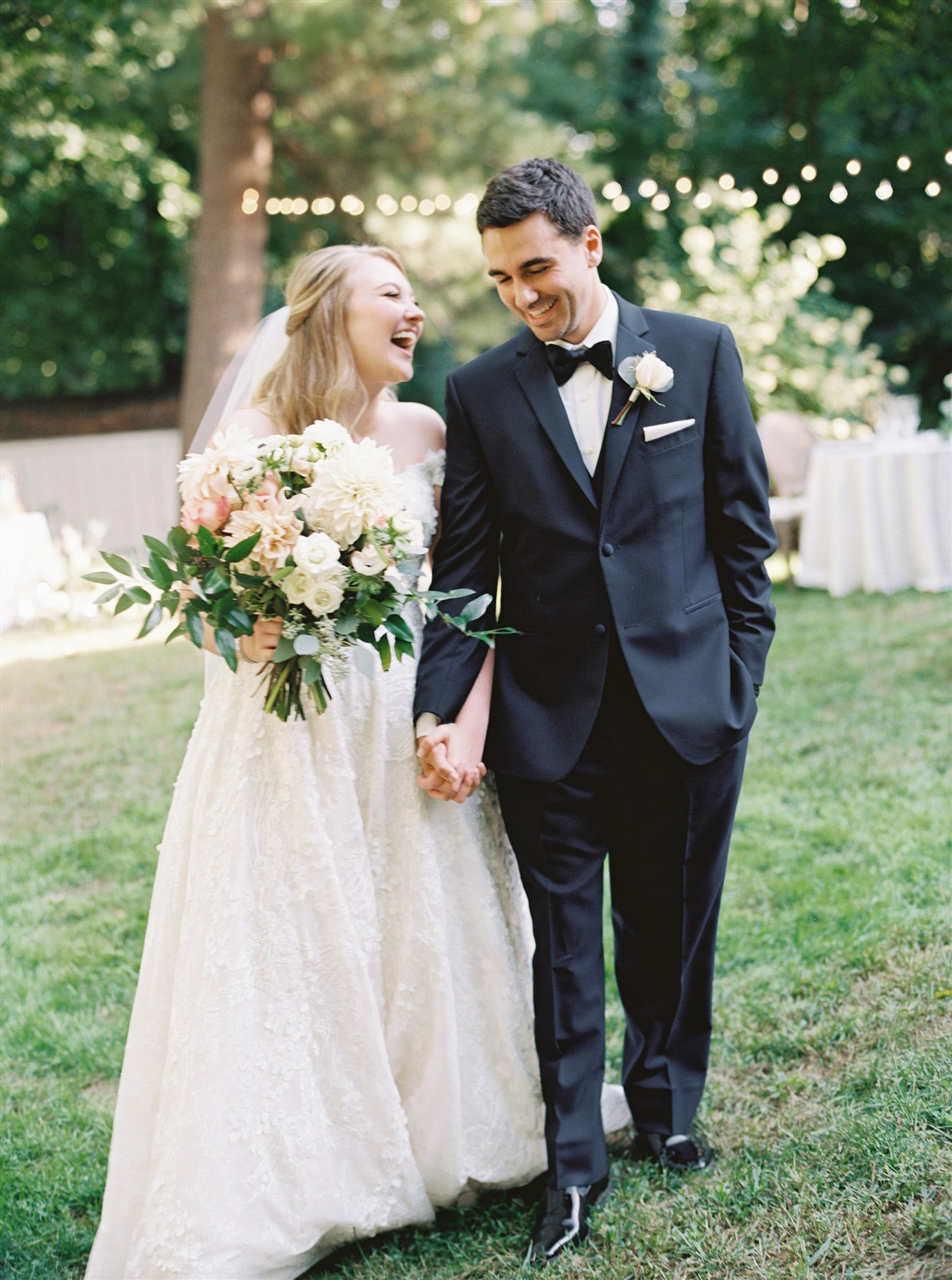 Bride and groom laughing while holding hands