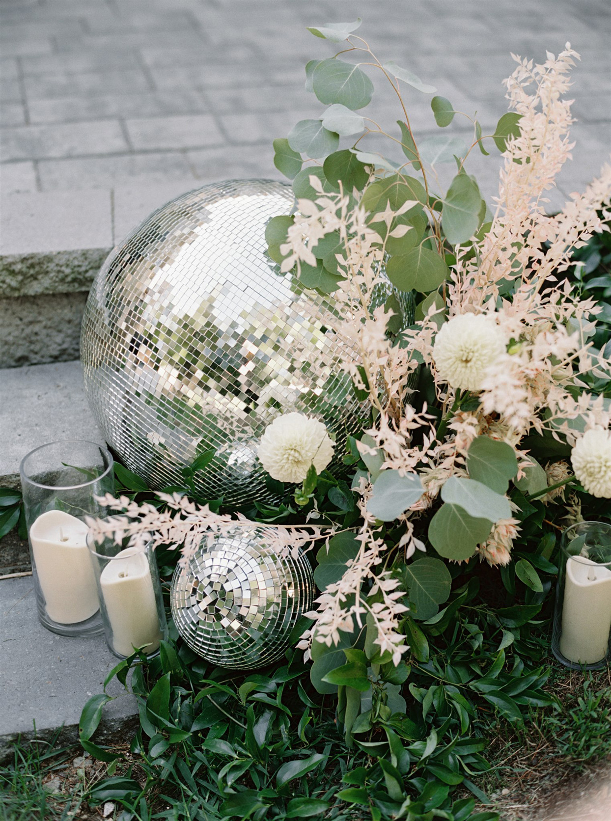 Disco ball surrounded by candles and greenery