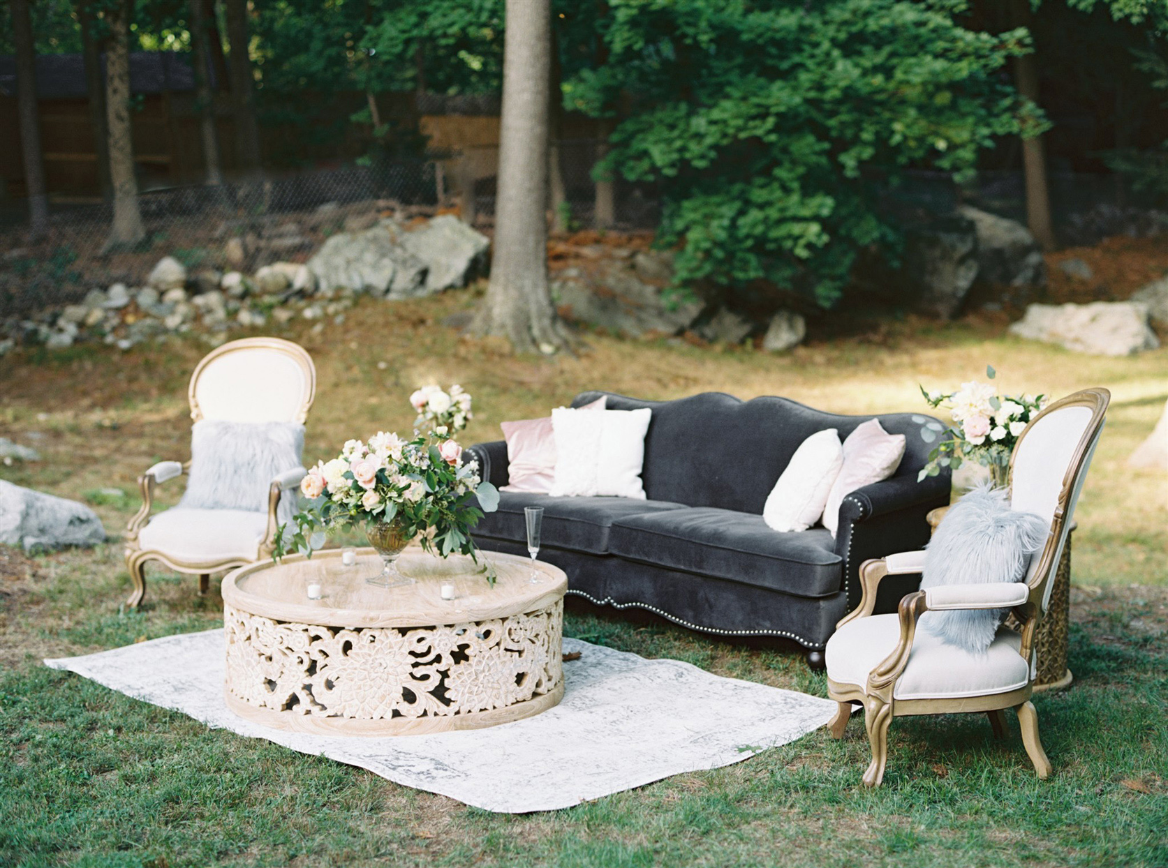 Couch and accent chairs in grass with coffee table