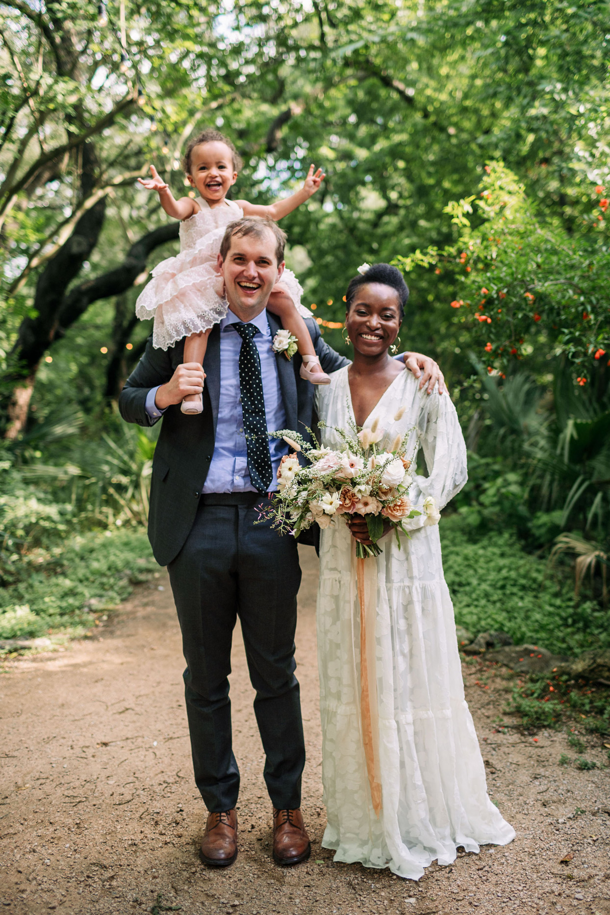 Bride and groom with flower girl in wooded area