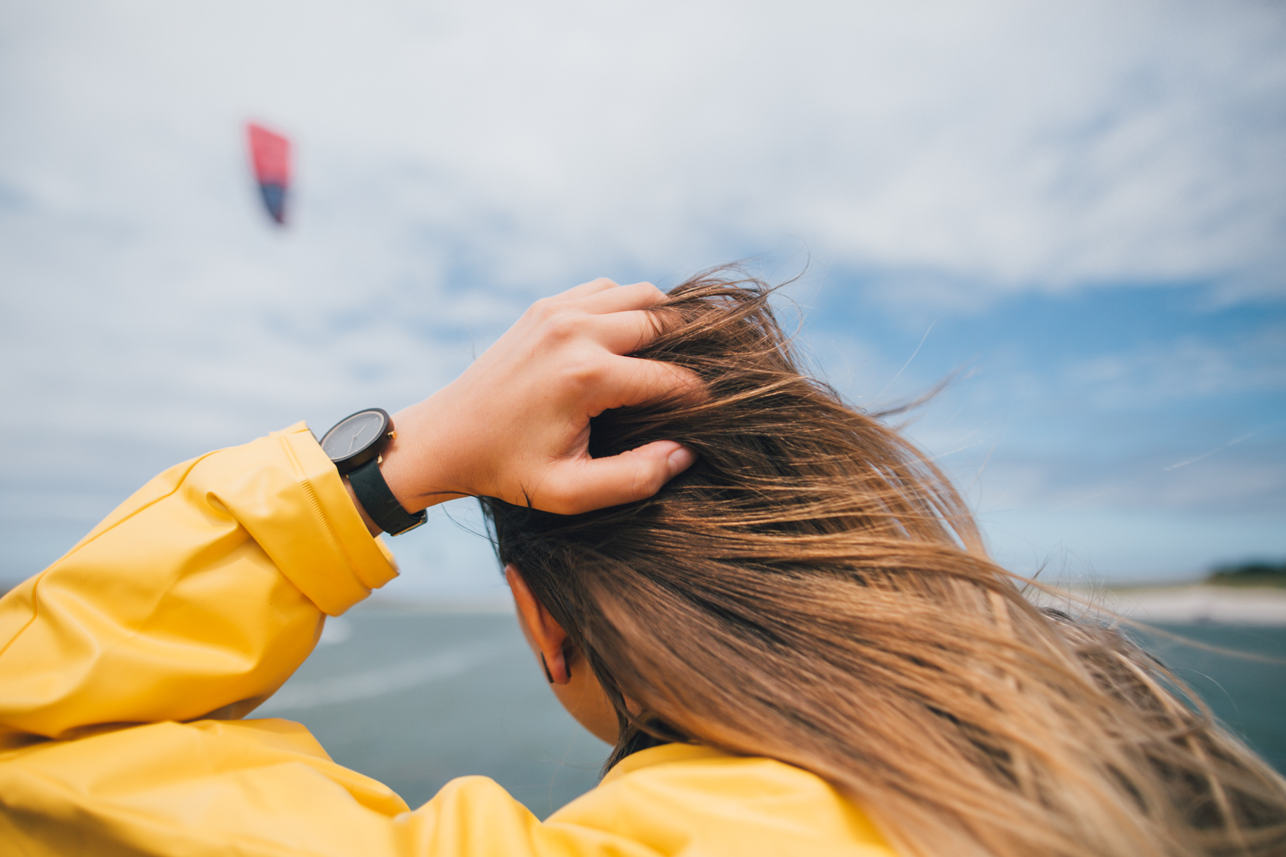 women holding hair on windy day