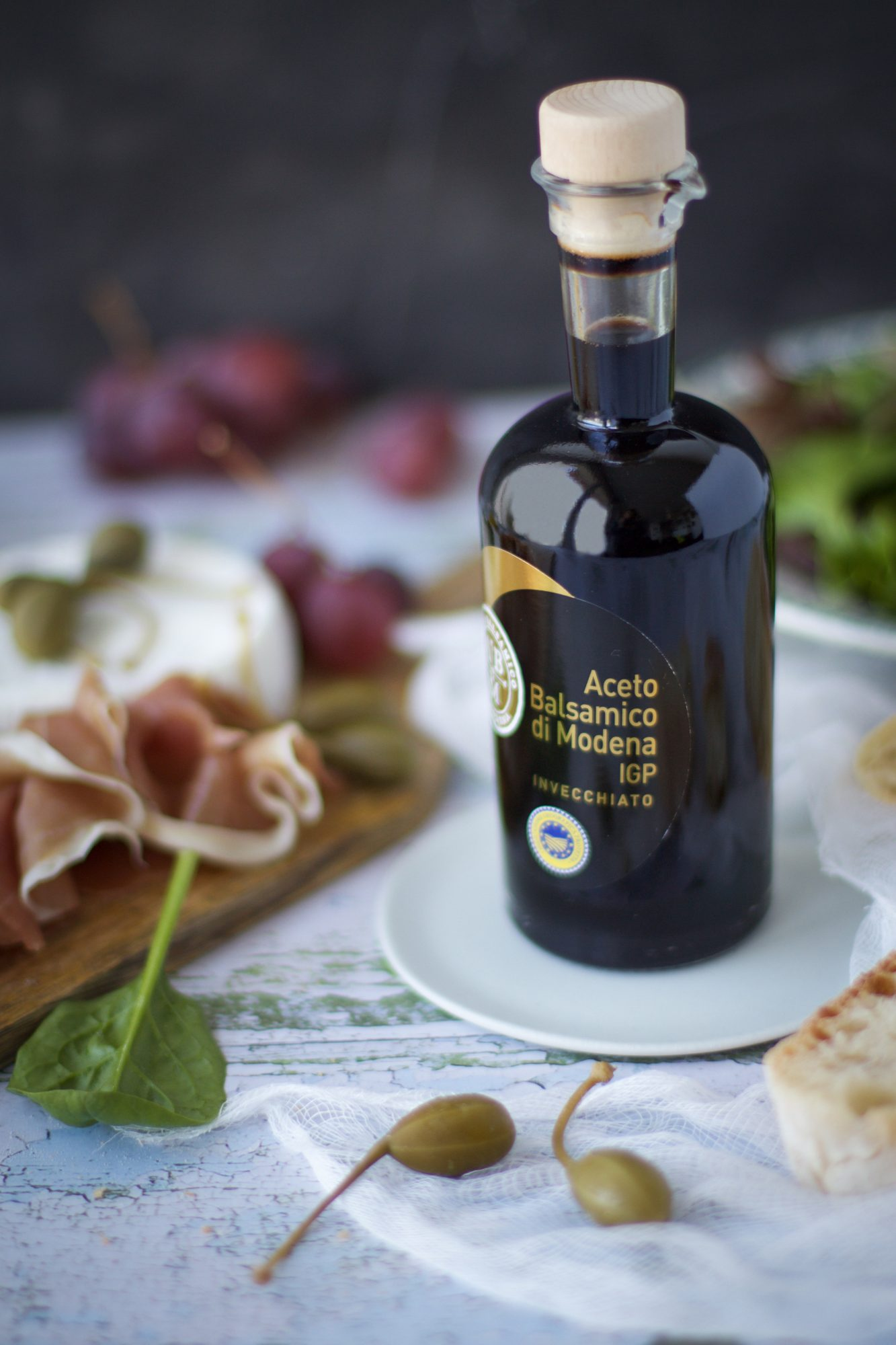 bottle of balsamic vinegar with proscuitto, caper berries, and bread