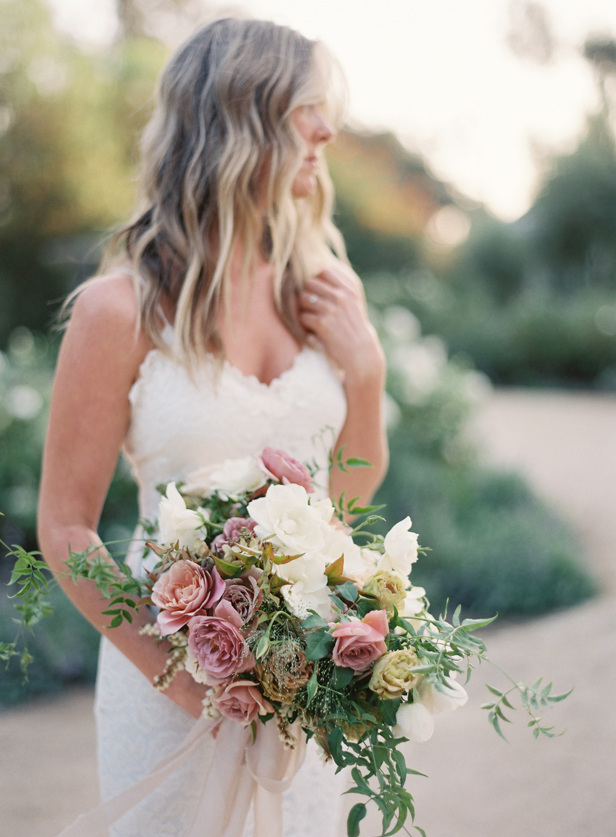 Bride with bouquet made up of blush flowers and greenery