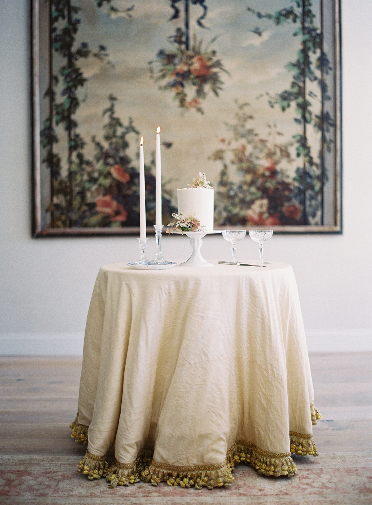 Cake table with candle, glassware, and two-tier cake