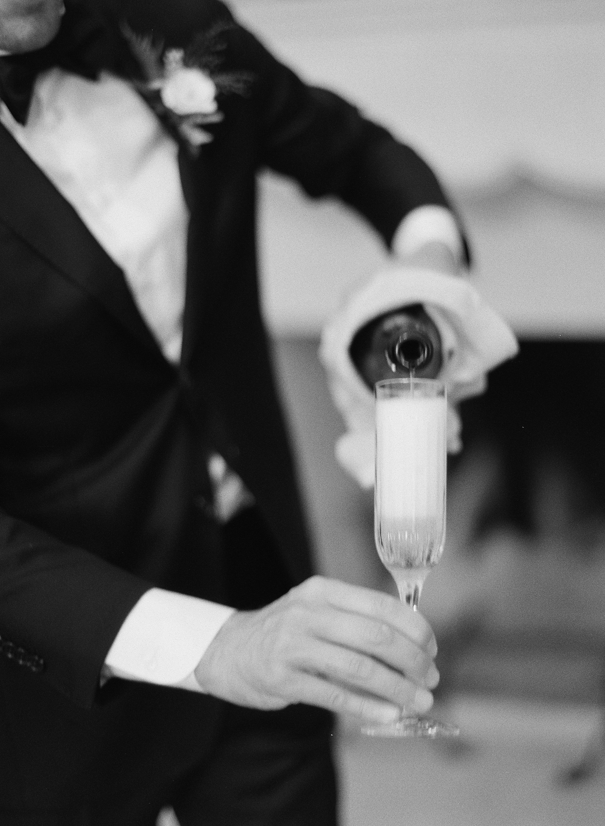 Groom pouring champagne into flute