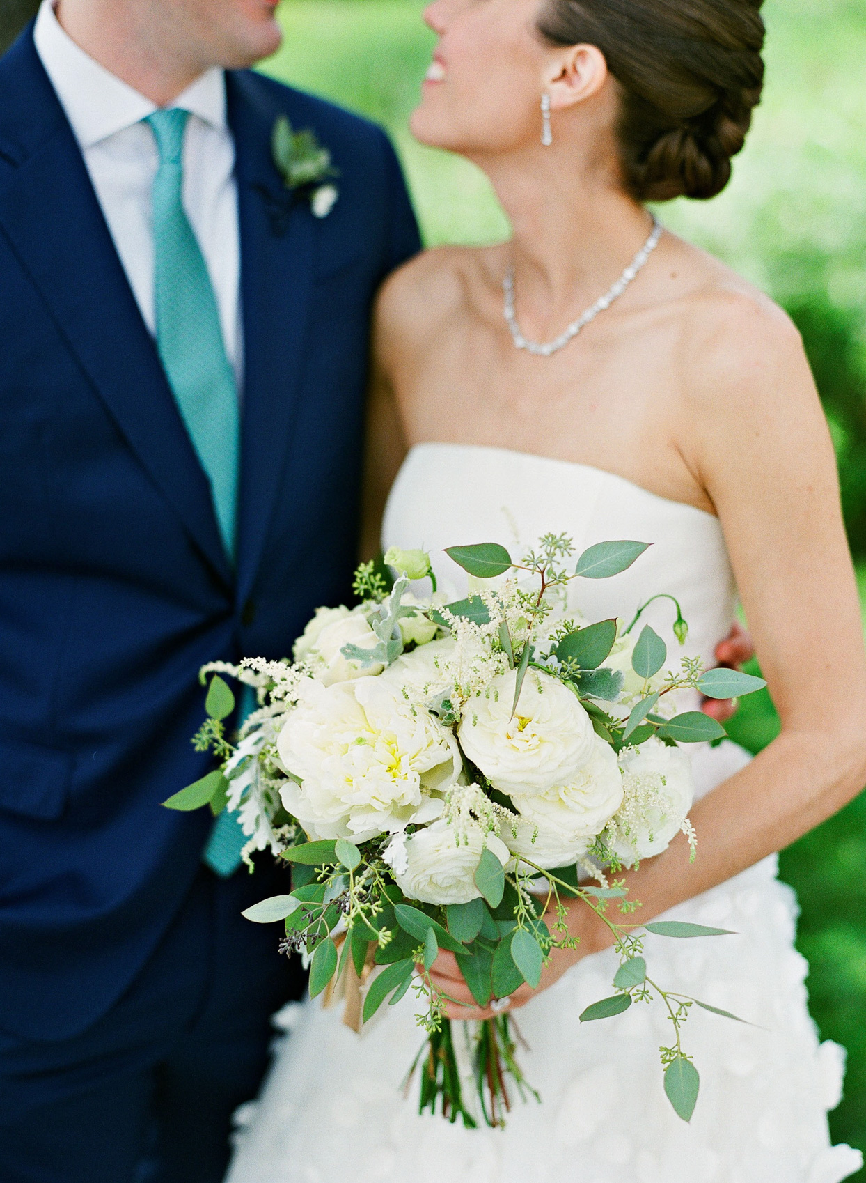 bride holding white floral bouquet for portrait with groom