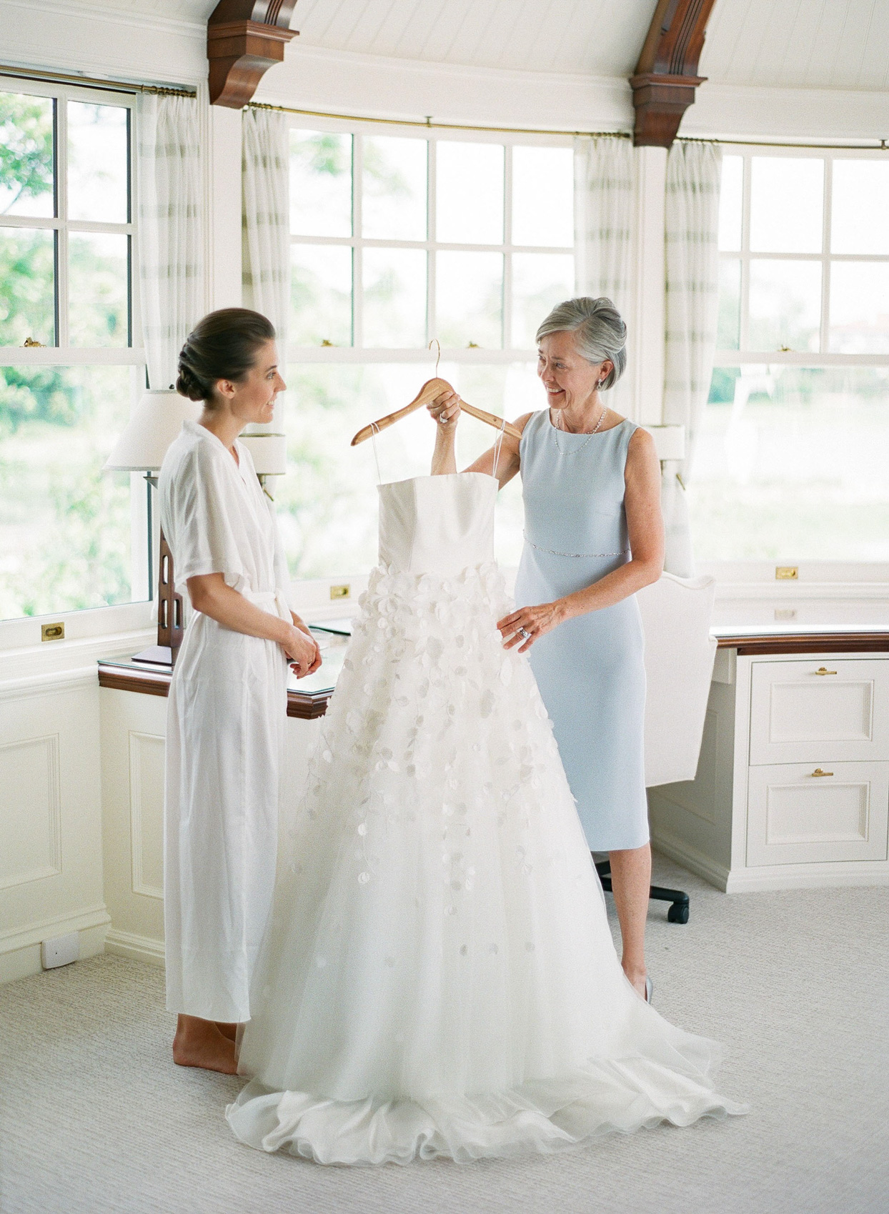mother holding wedding dress with bride