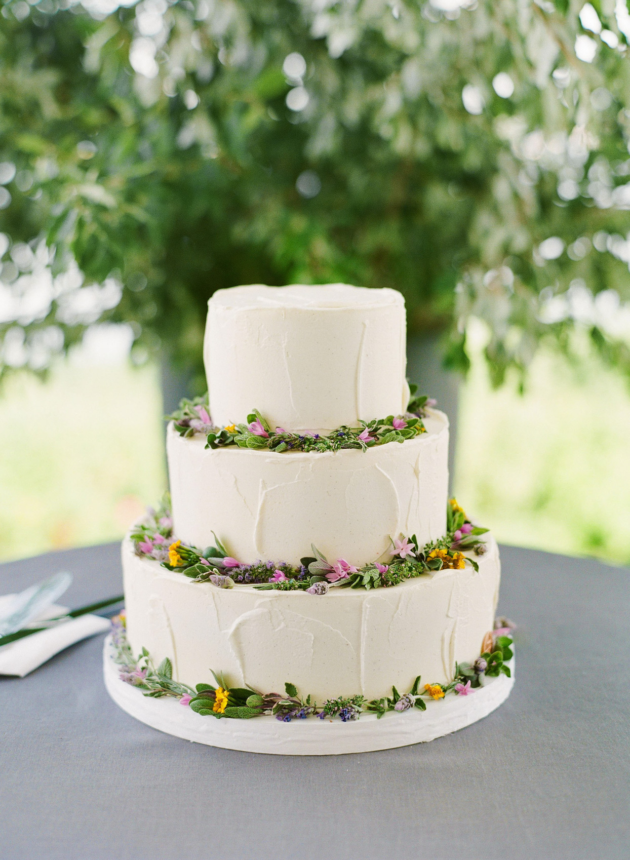 three tiered wedding cake with delicate wild flower decorations