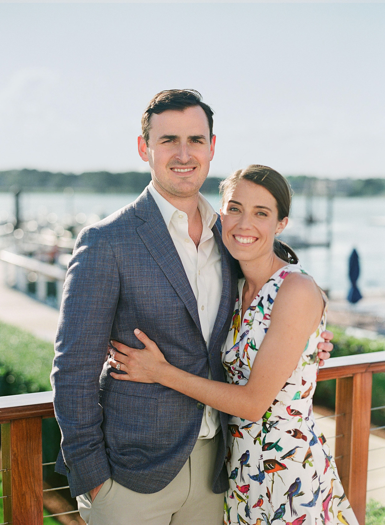 couple in casual rehearsal dinner outfits portrait with water view