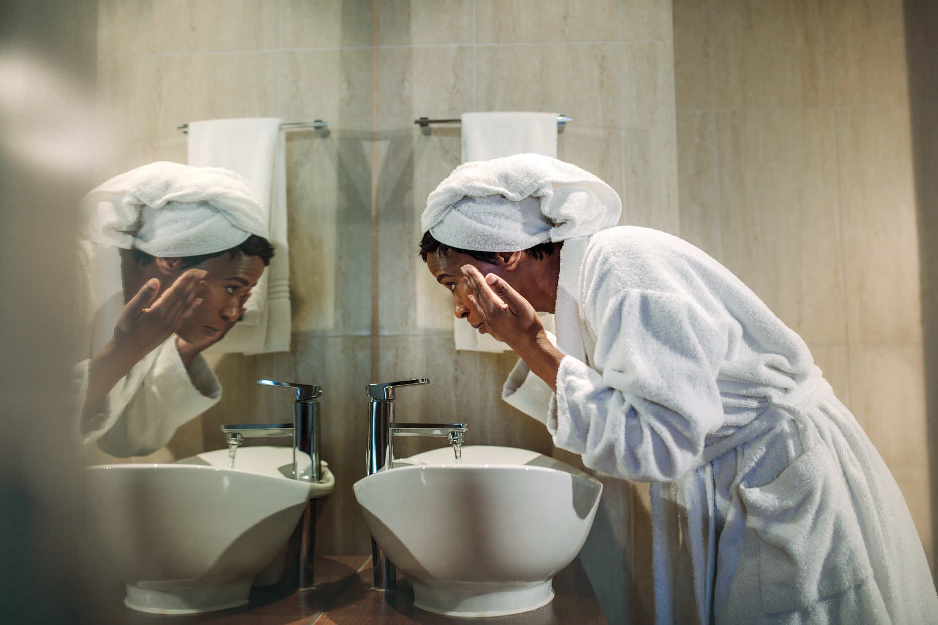 woman wearing towel and robe washing face