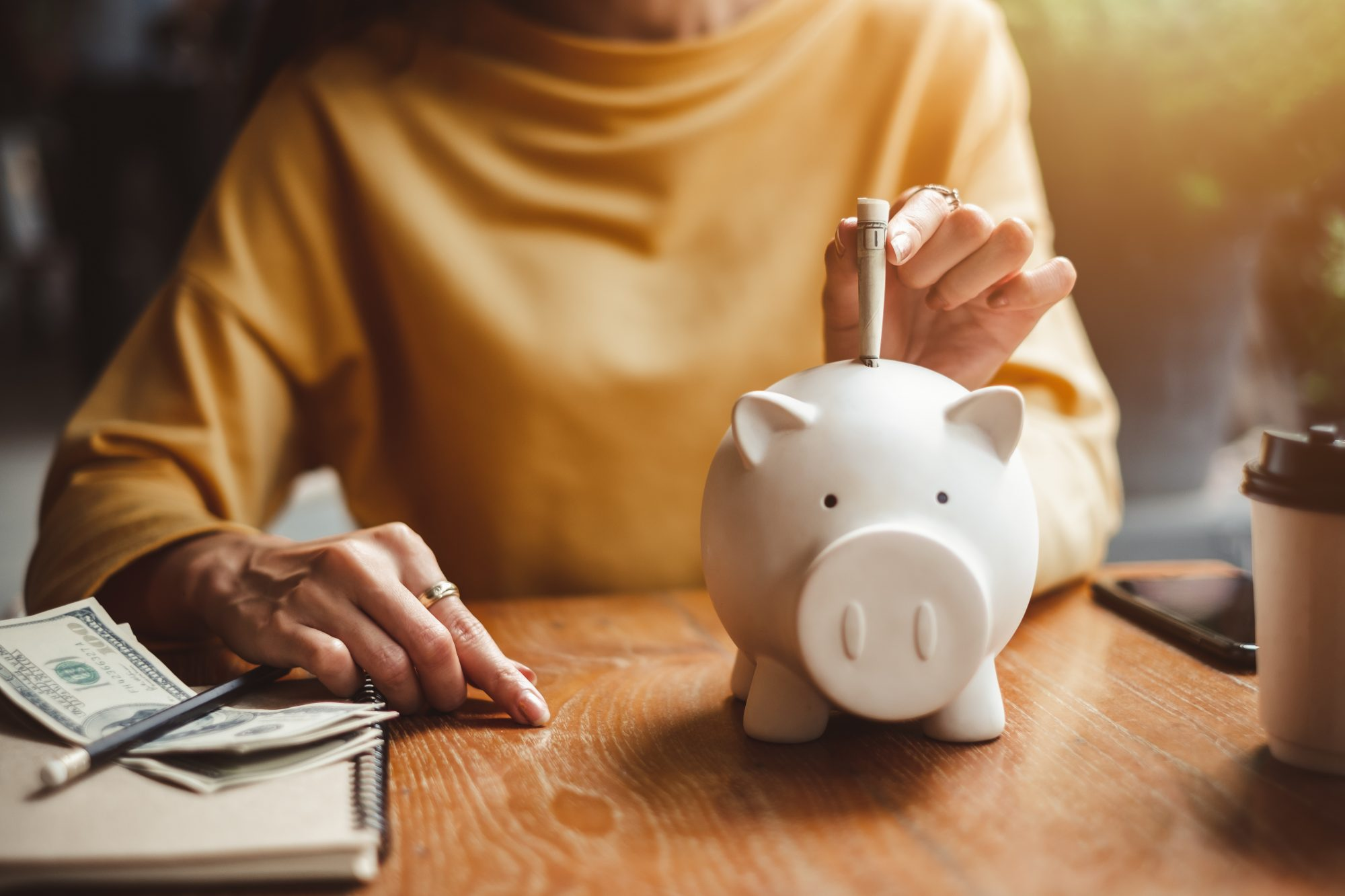 woman sitting at a table and adding money in a piggy bank