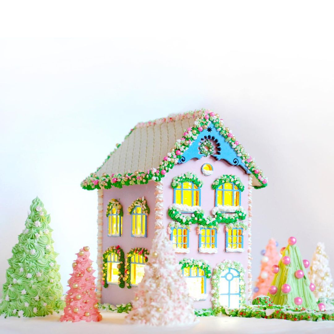 bright and colorful gingerbread house surrounded by matching decorative trees