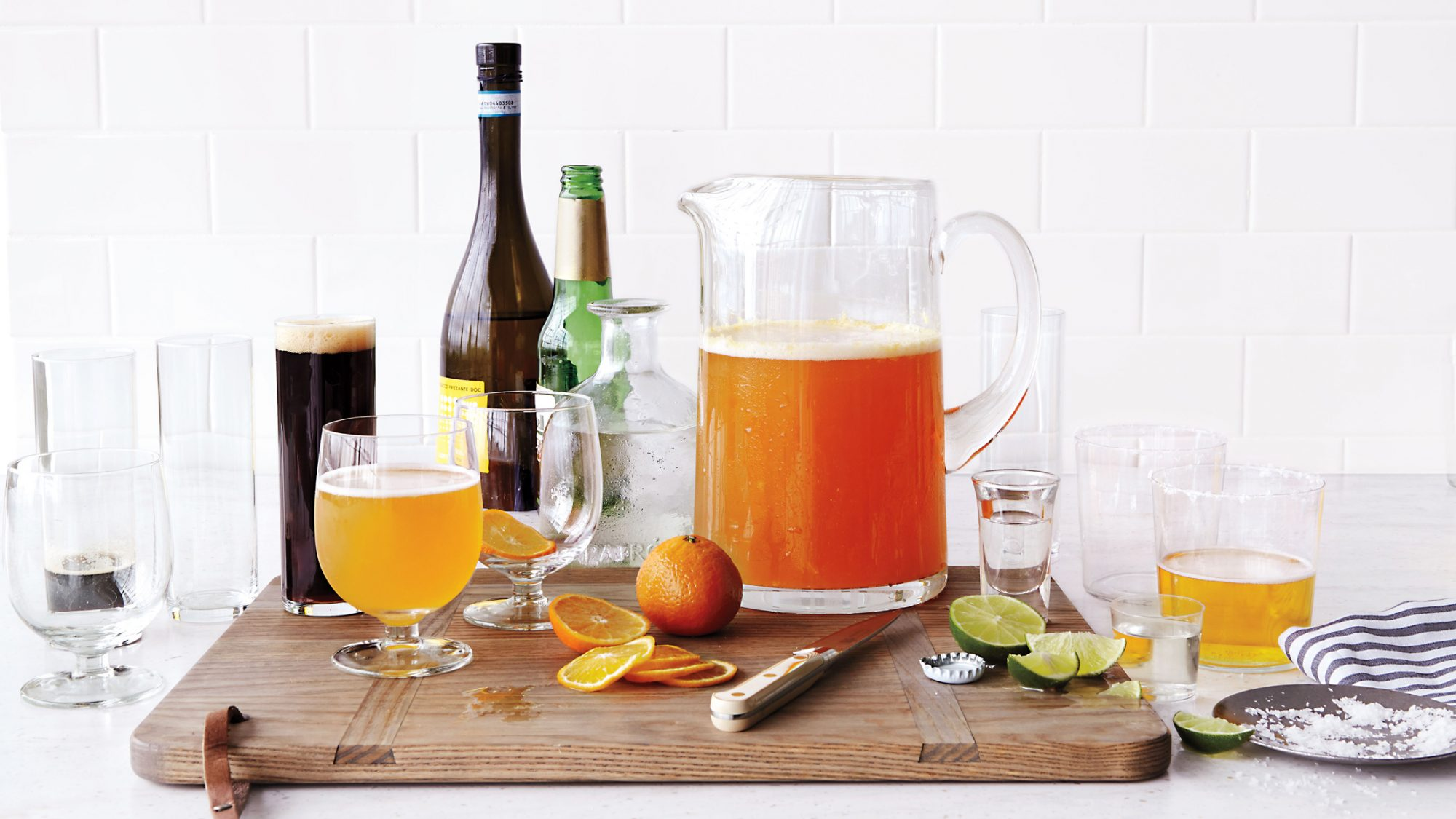 pitcher of beer and sliced oranges and limes atop cutting board