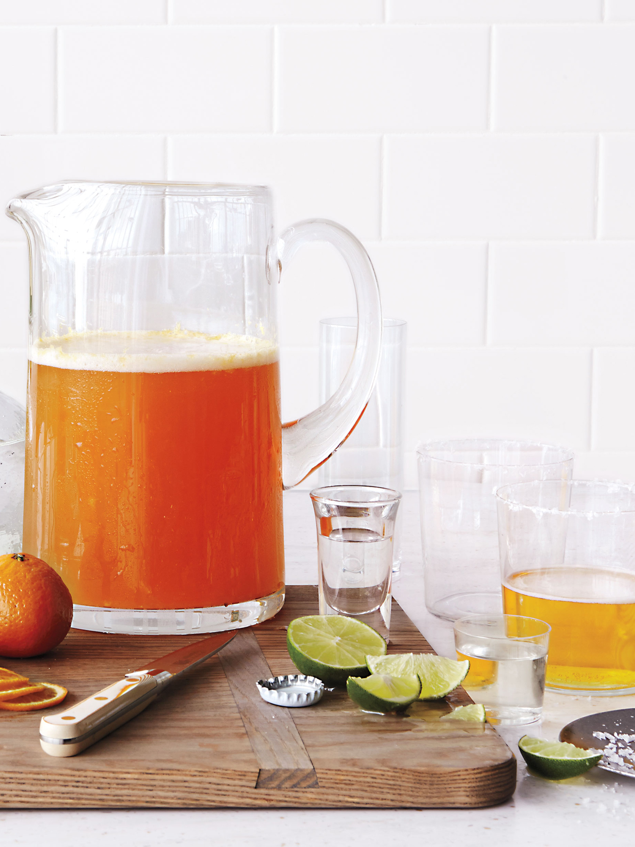 pitcher of beer shot glass and sliced limes atop cutting board