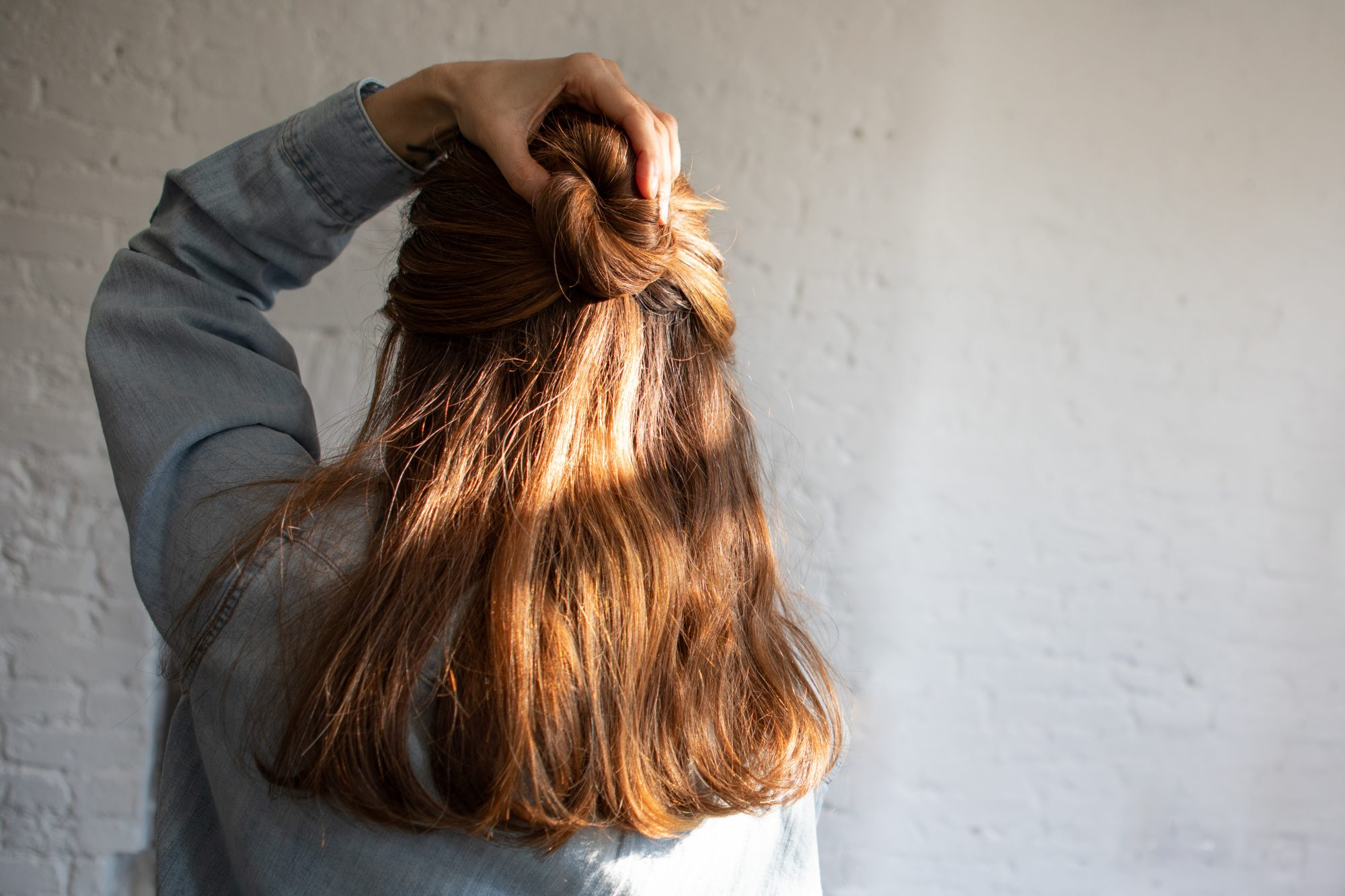 woman touching hair in a half bun and down style