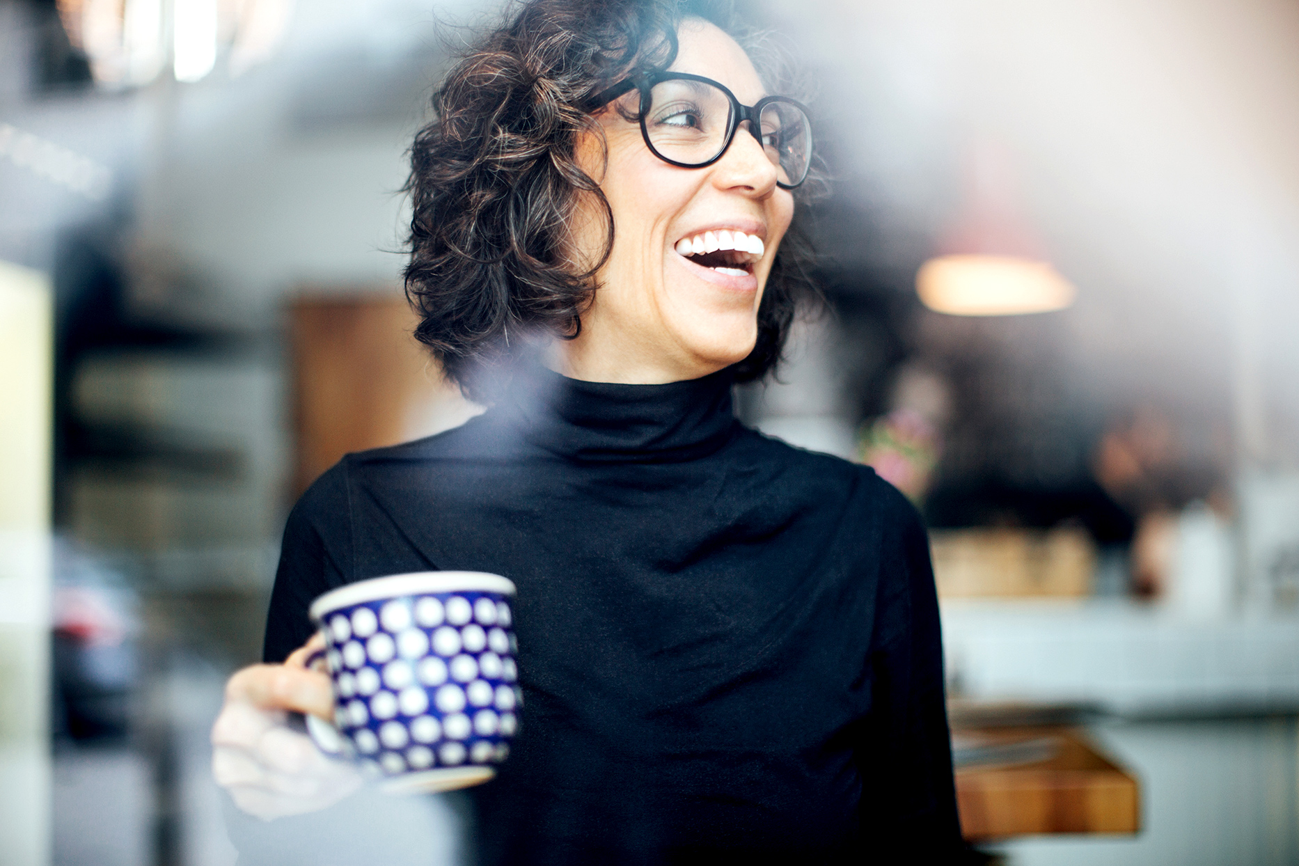 person holding coffee cup laughing
