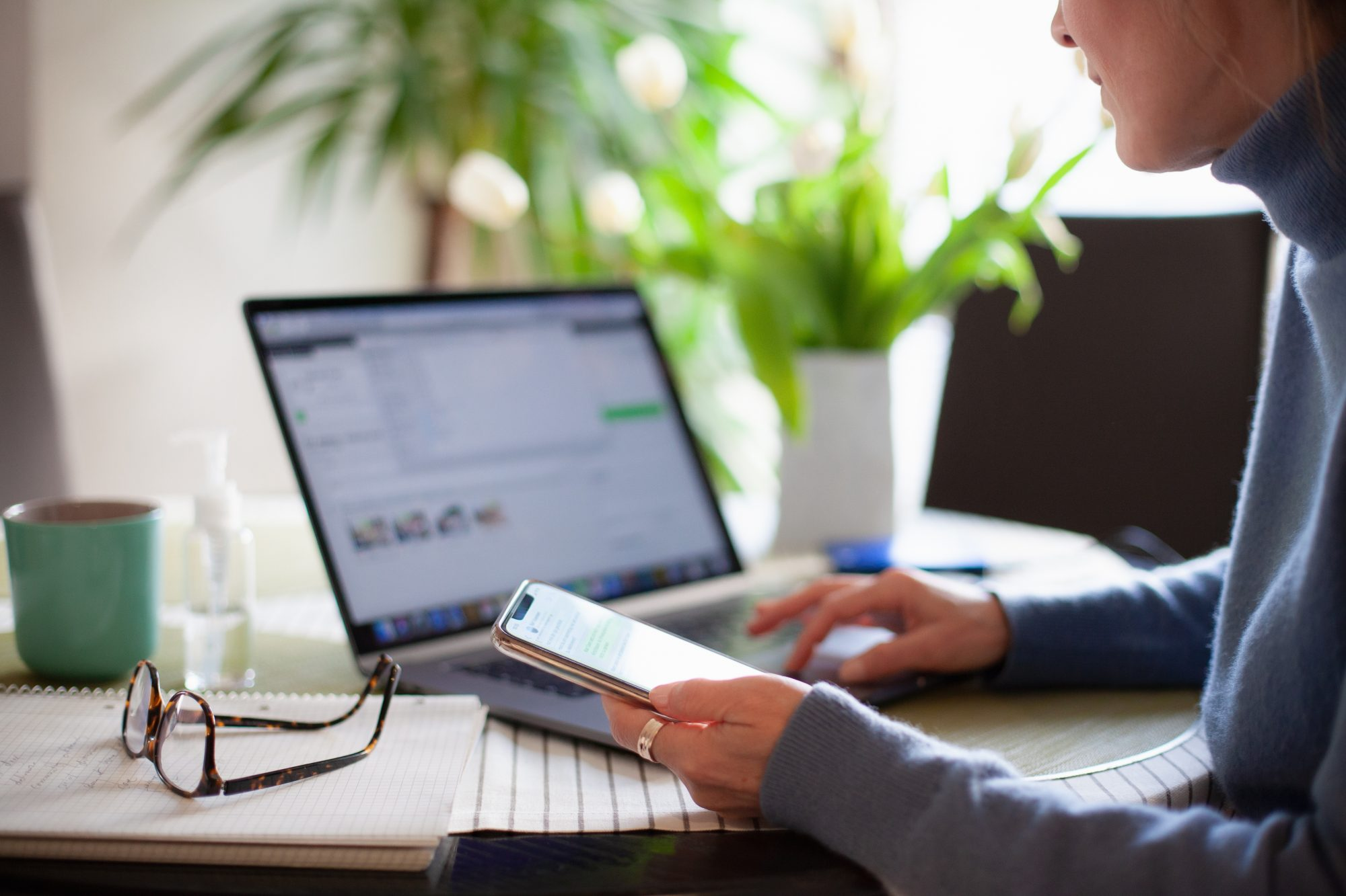 Woman working from home using laptop computer while reading text message on mobile phone