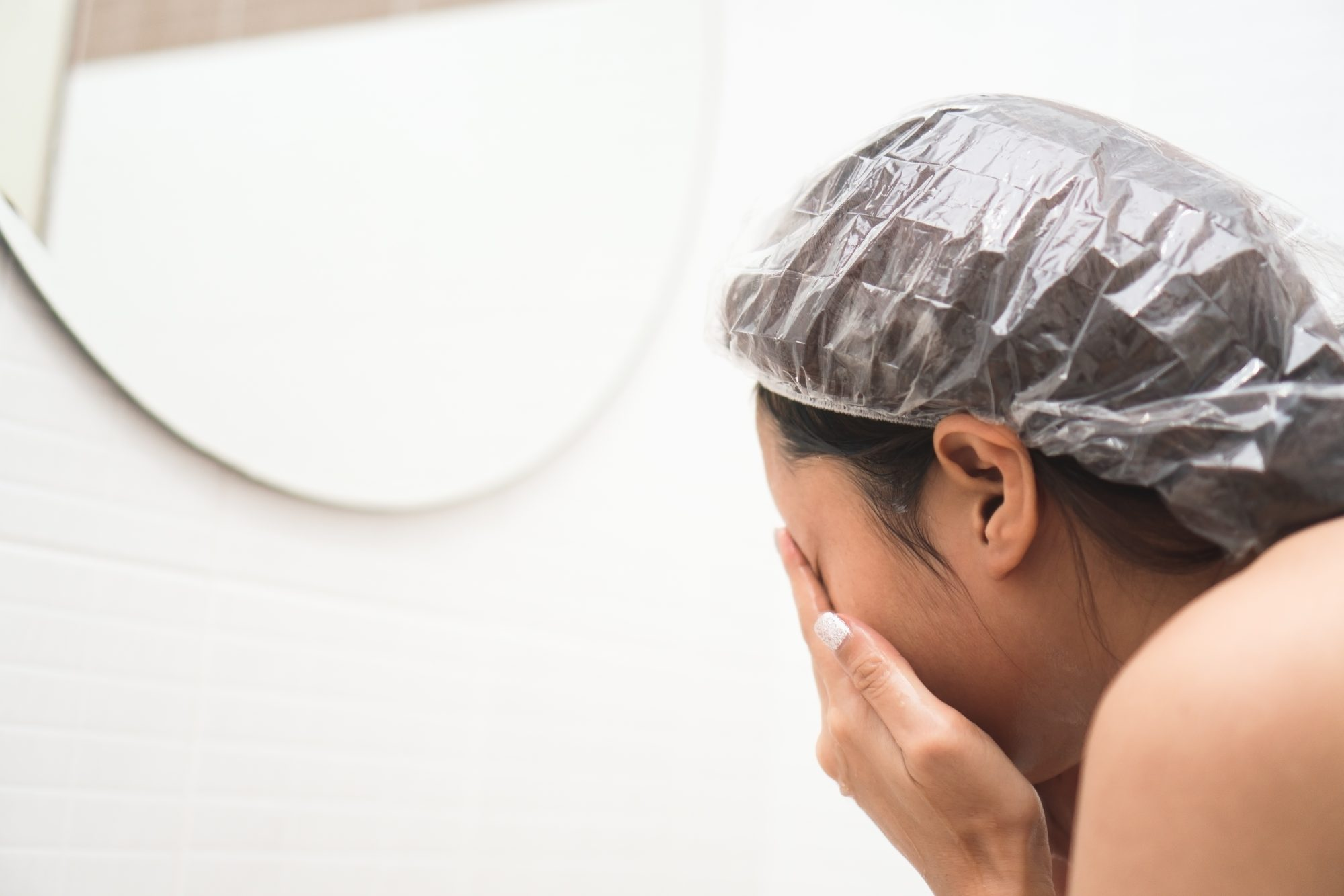 Young woman wearing a shower cap and washing face in the bathroom