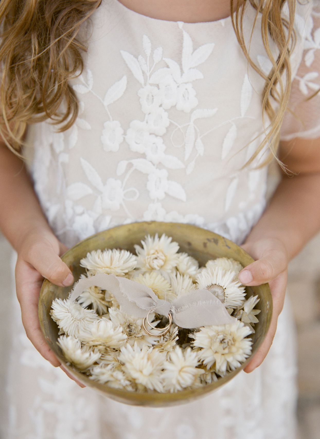 Flower girl holding bowl with wedding bands