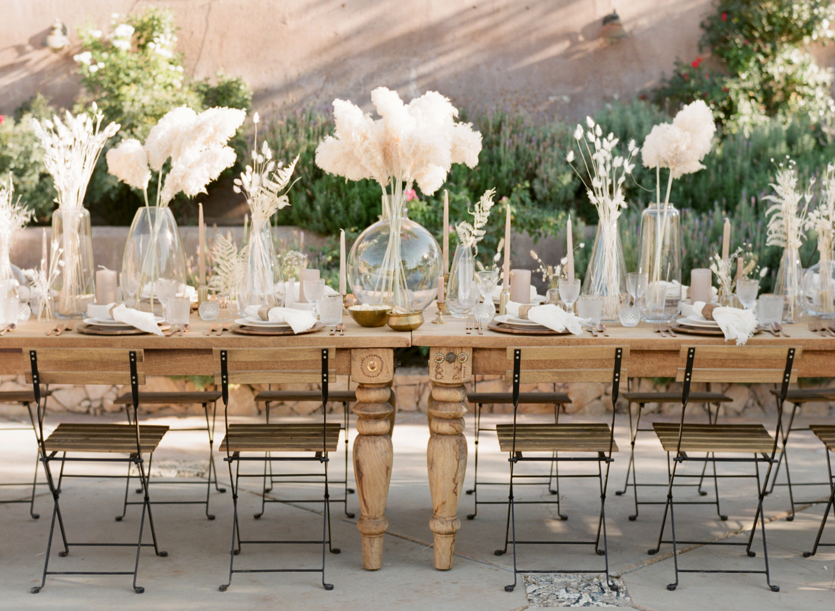 Long table set with candles, flowers, and plates