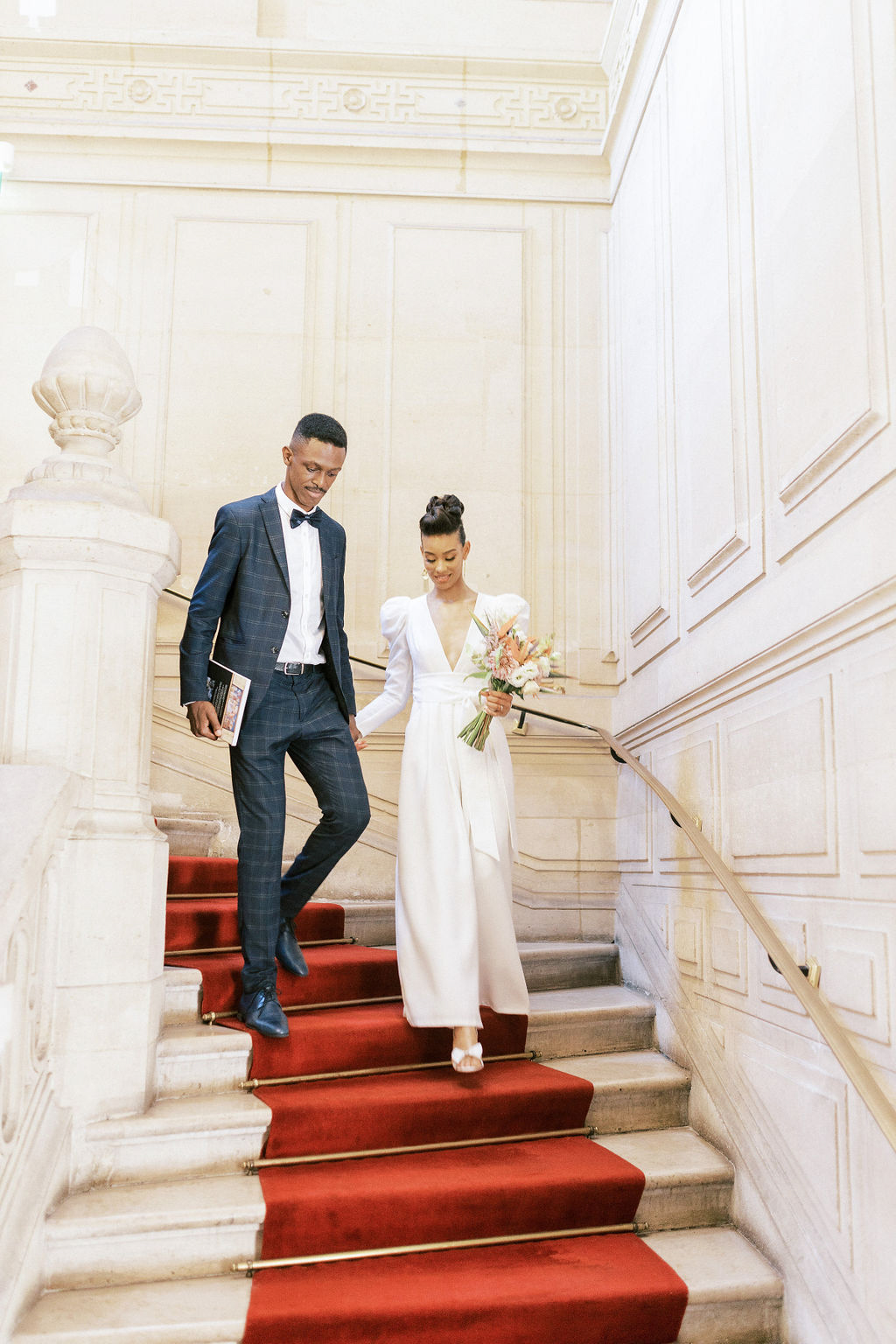 couple walking down red carpeted stairs together