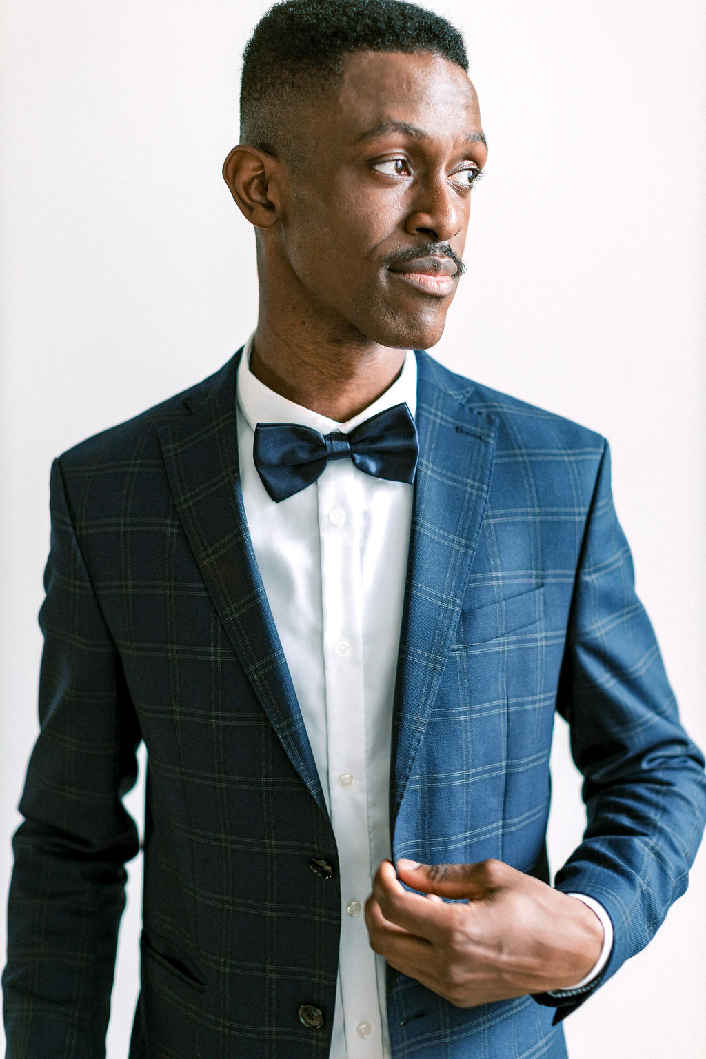 groom in plaid navy suit and bow tie