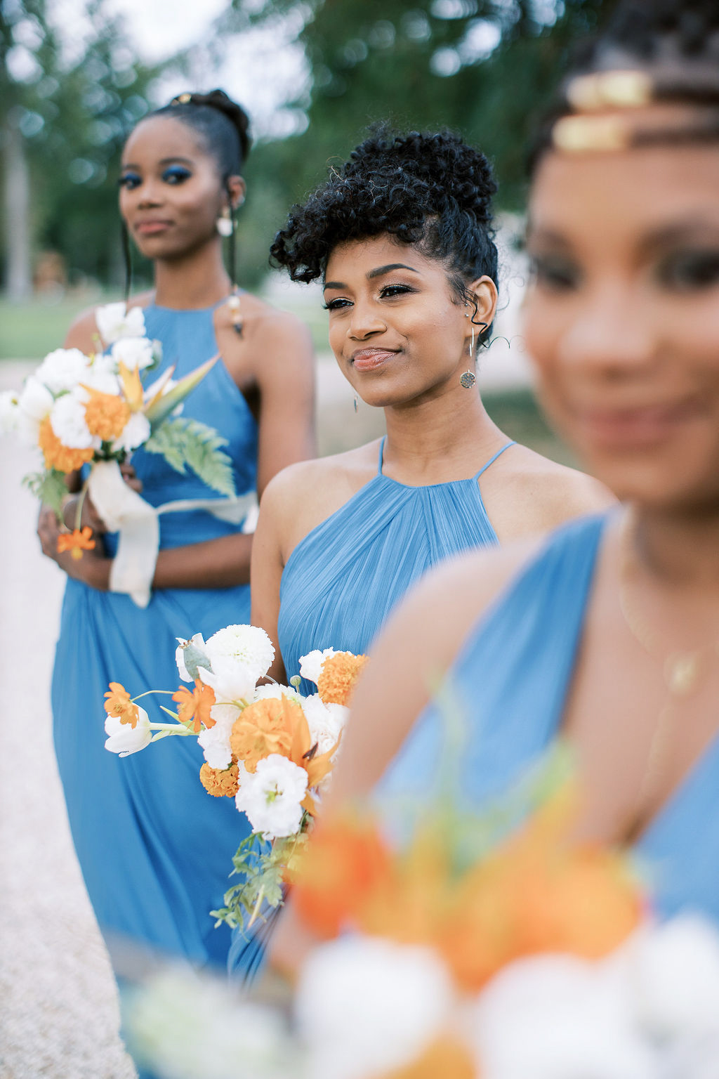 bridesmaids in blue dresses holding orange and white flowers