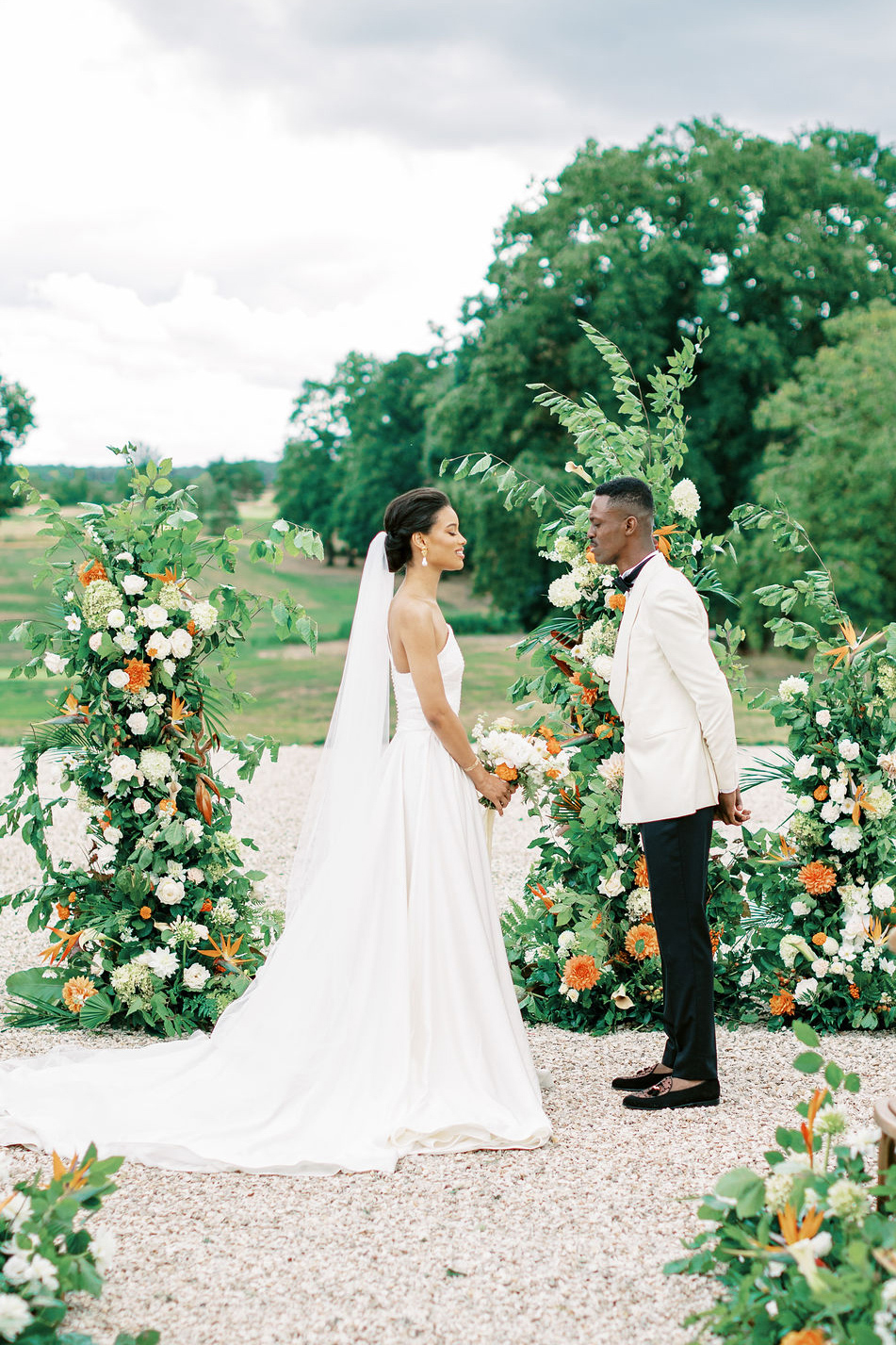 couple during outdoor ceremony in front of elegant floral installments