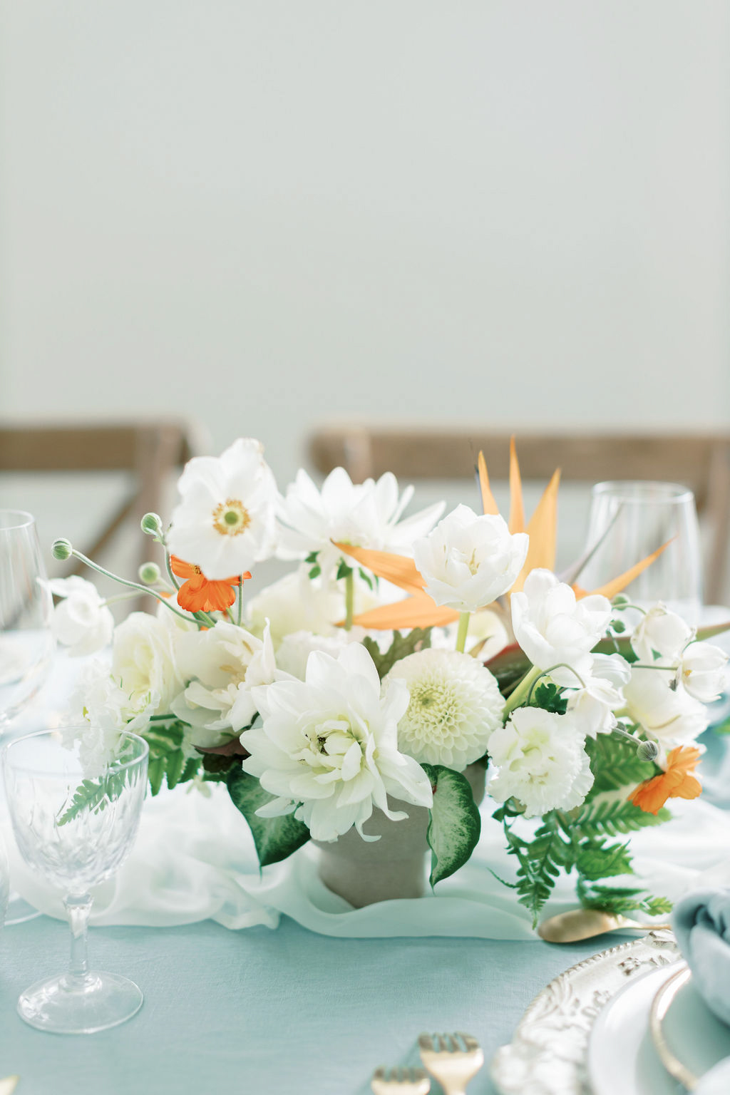white and orange floral wedding centerpiece on blue table