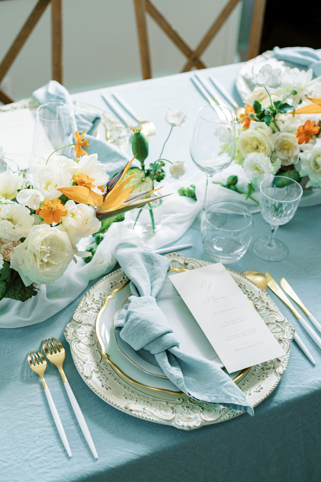 elegant blue, white, and orange place settings with ornate plates and silverware
