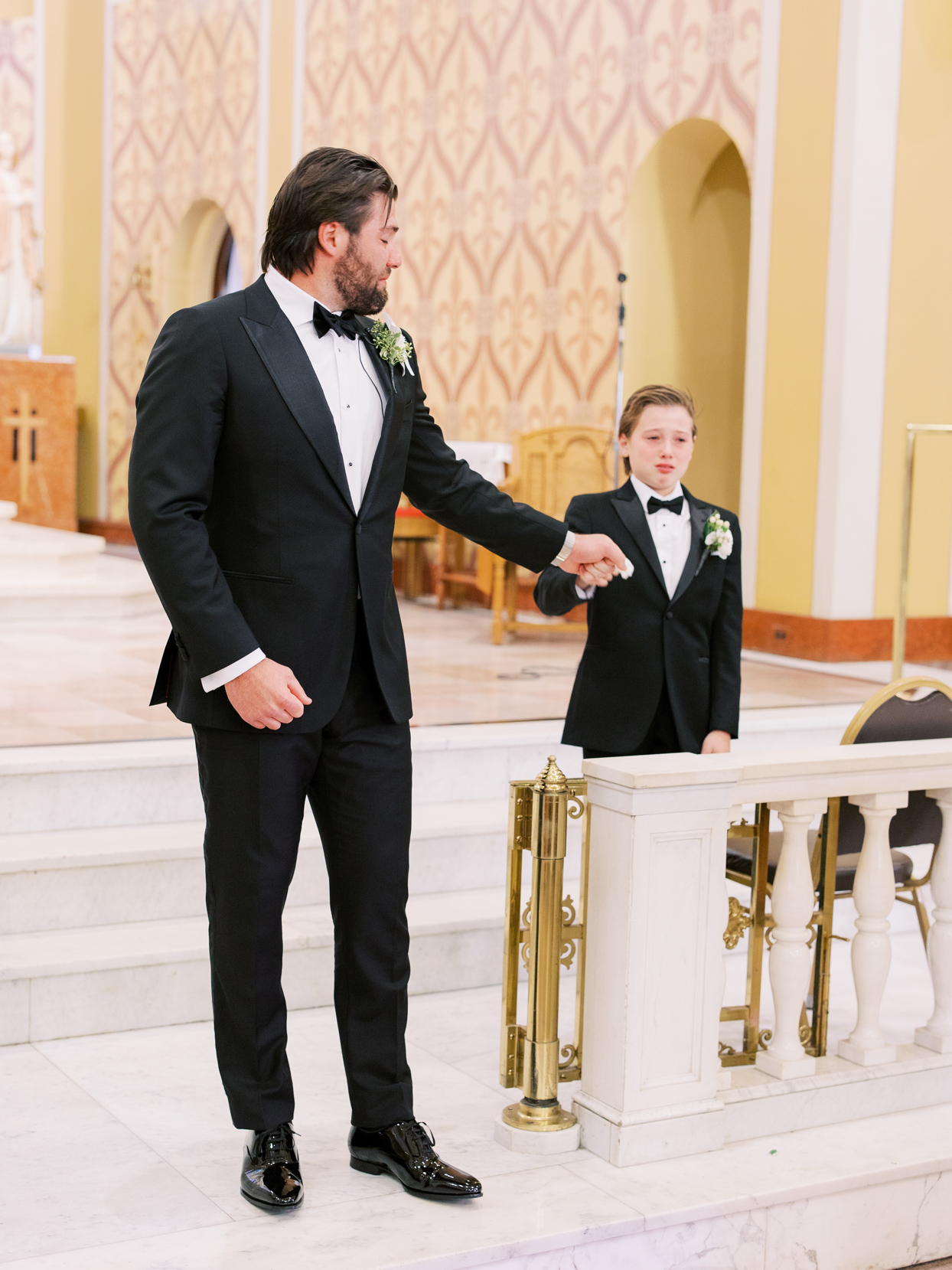 groom and son holding hands in church