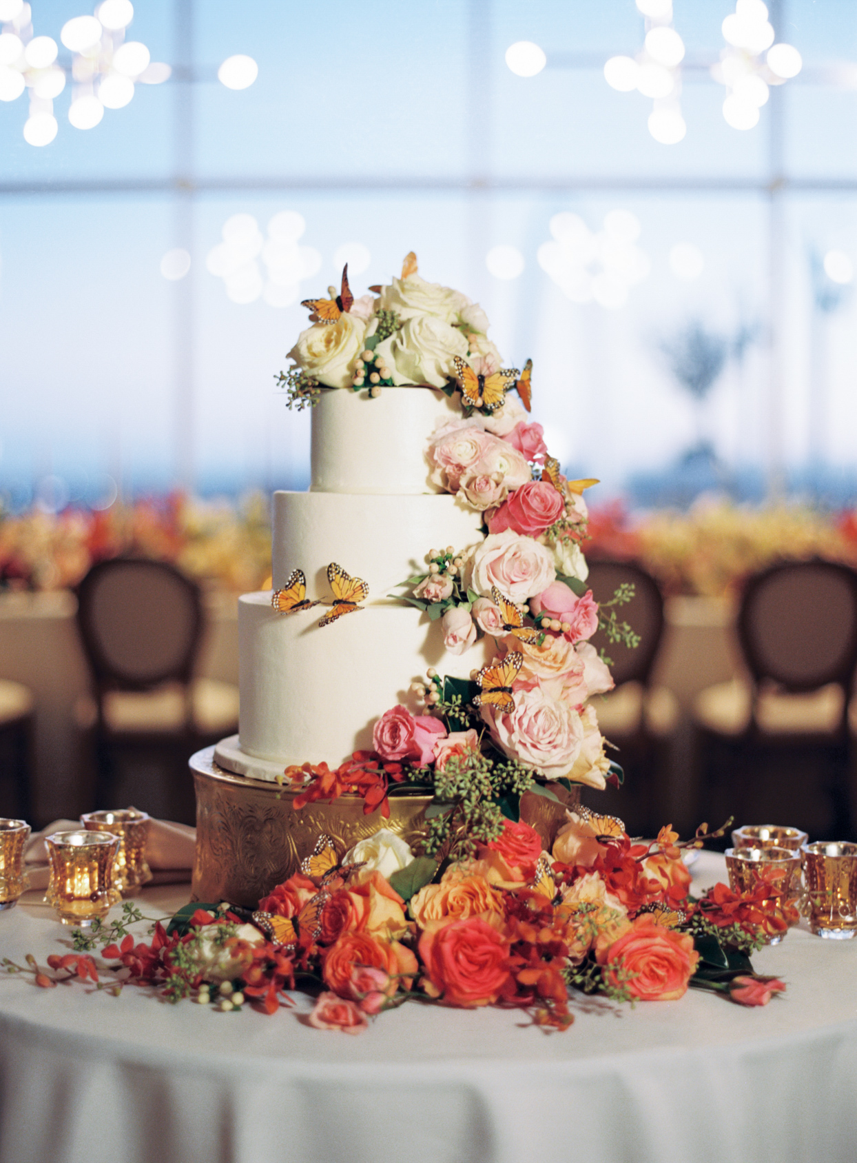 elegant white wedding cake with floral and butterfly garland