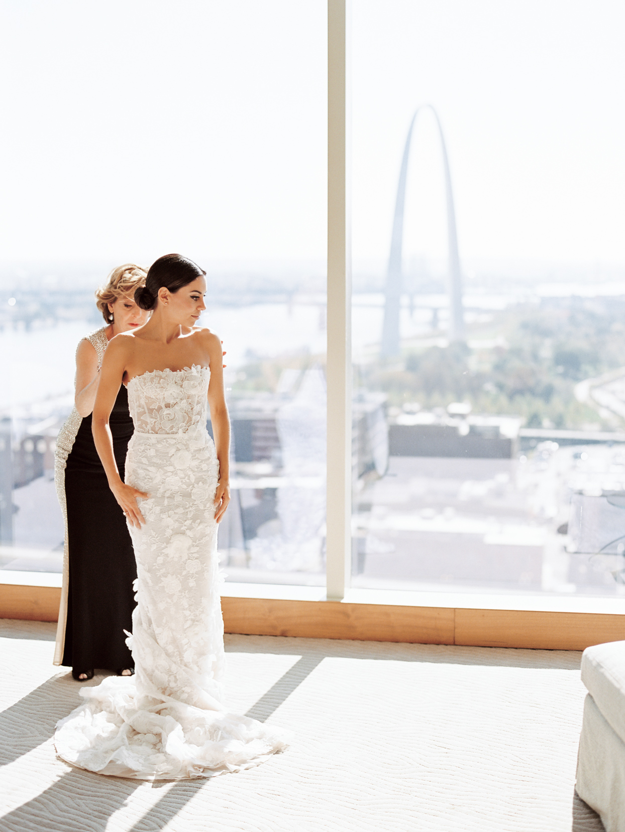 mother helping bride put on her dress with skyline view