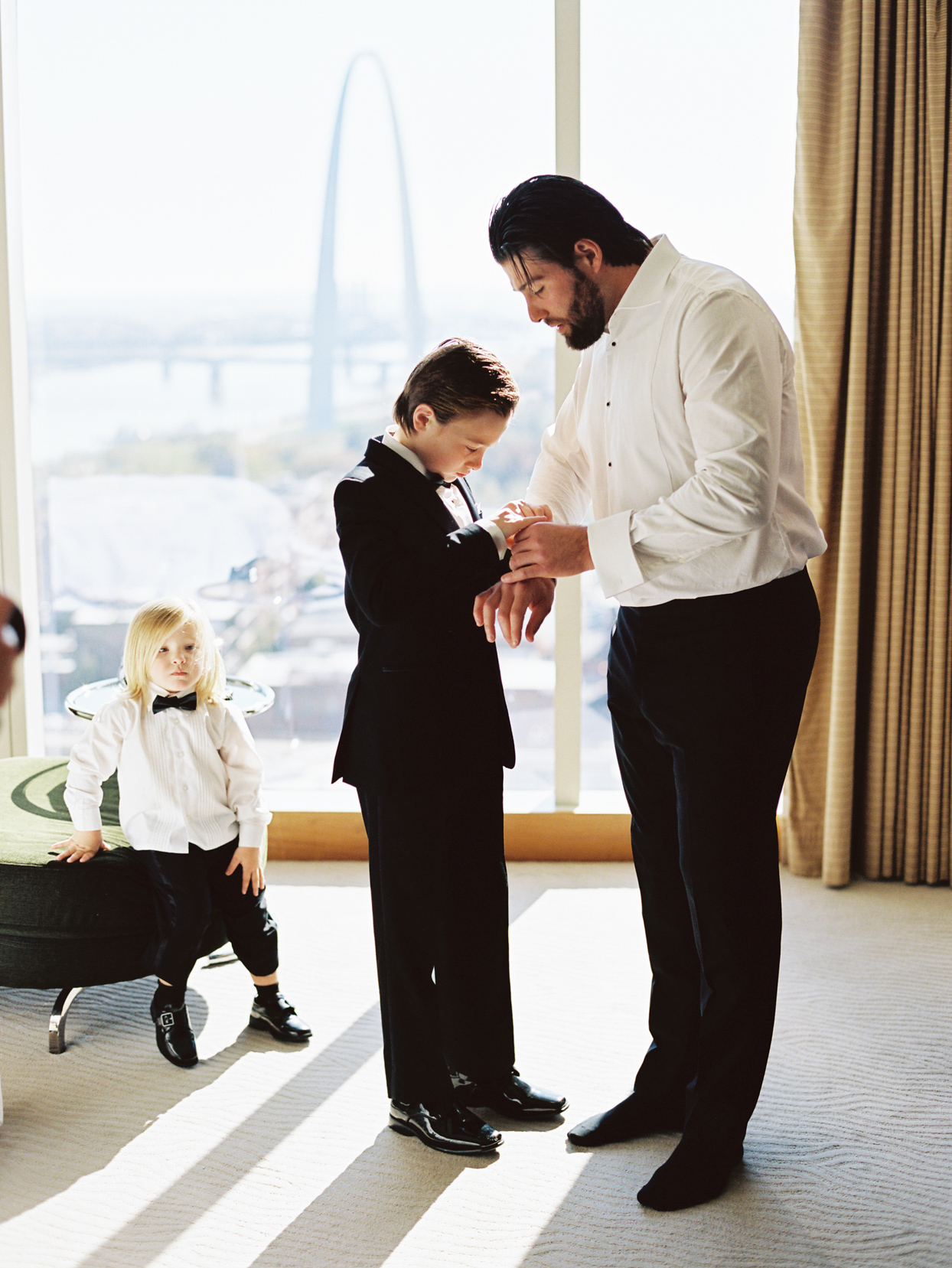 groom and son getting ready for wedding with skyline view