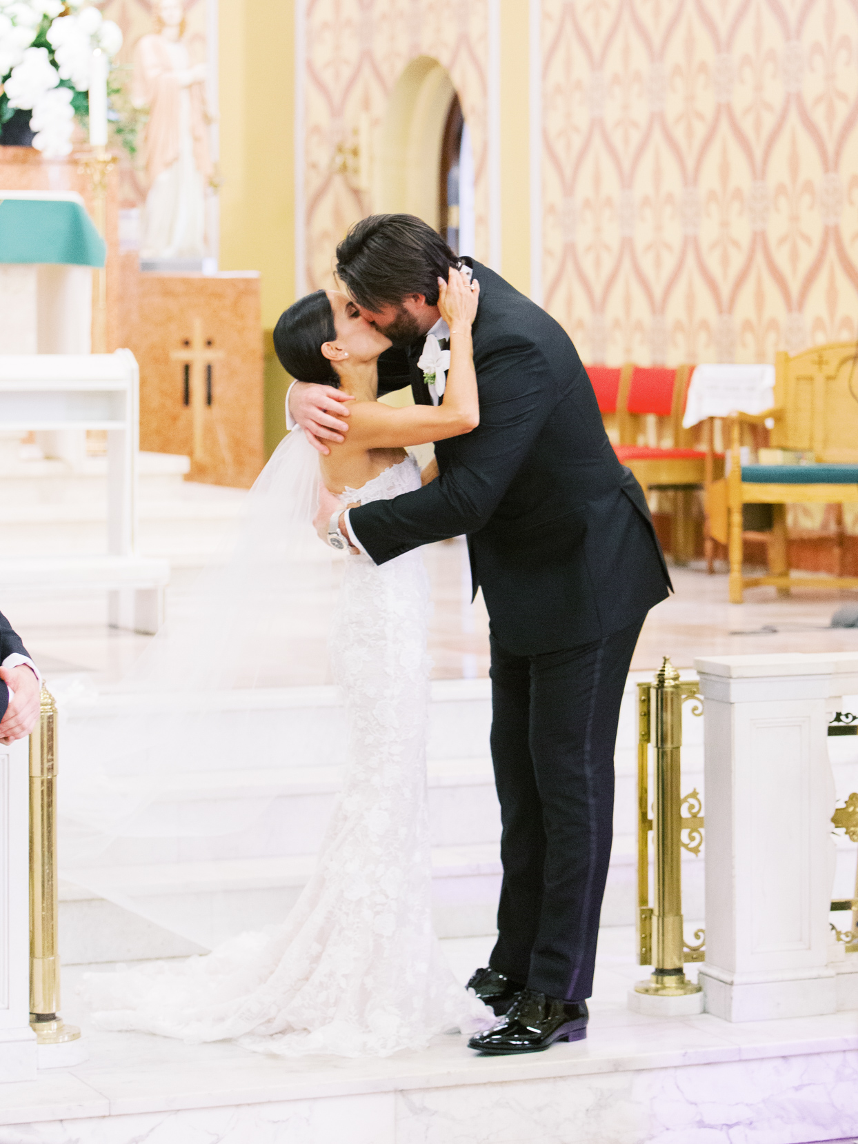 wedding kiss on marble stairs in catholic church