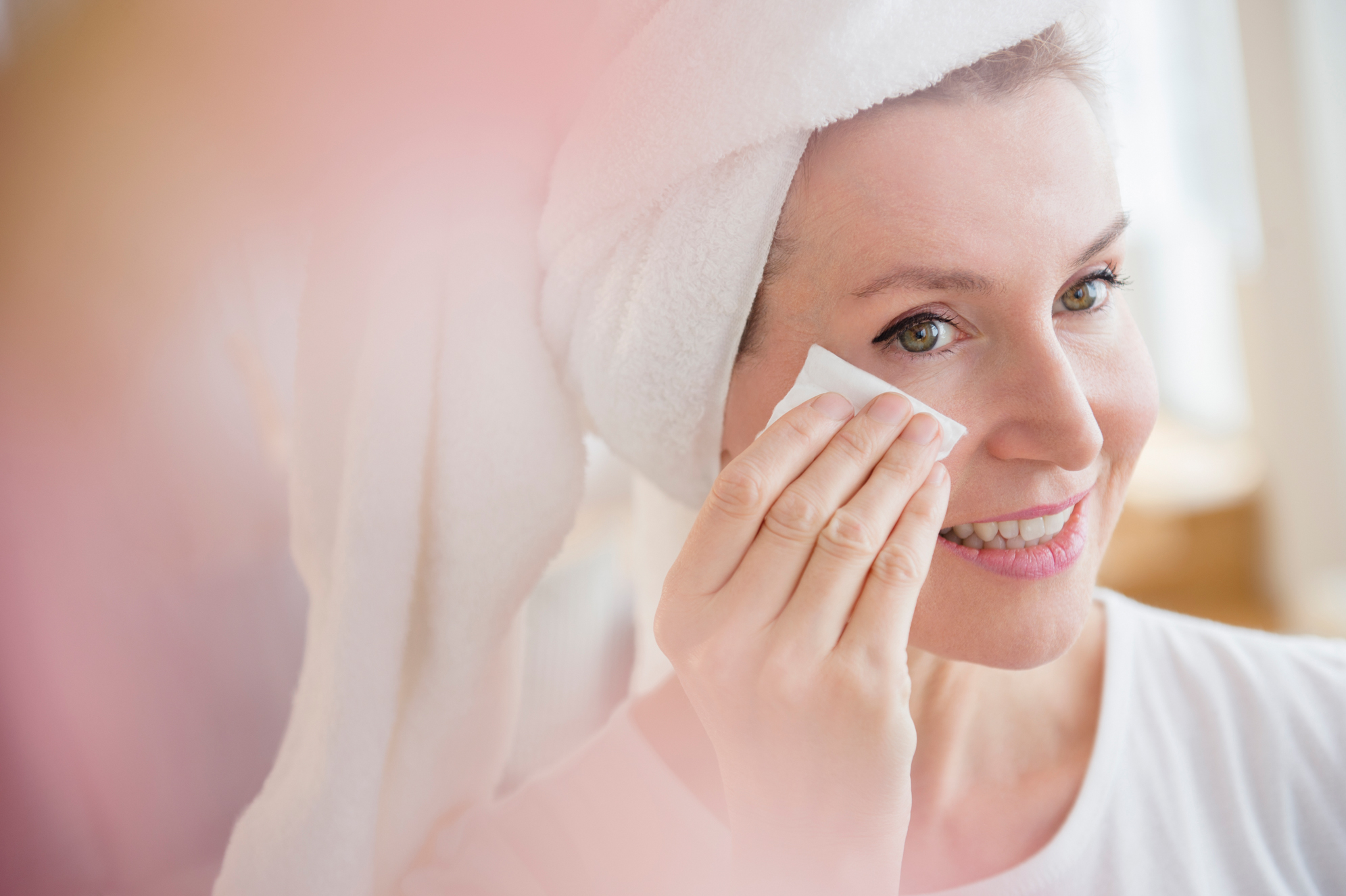 person with hair wrapped in towel wiping face with skin care towelette