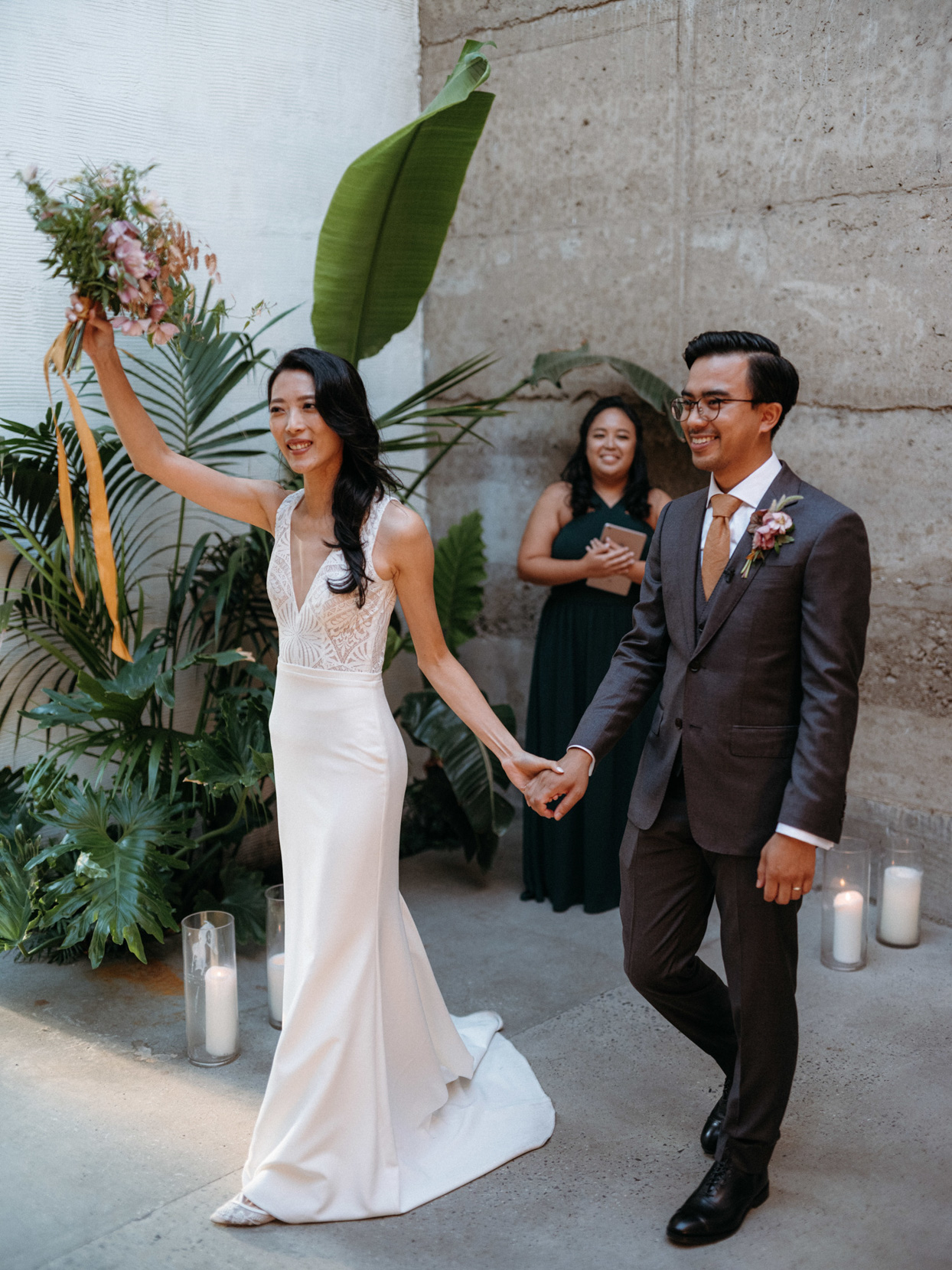 couple holding hands at warehouse ceremony