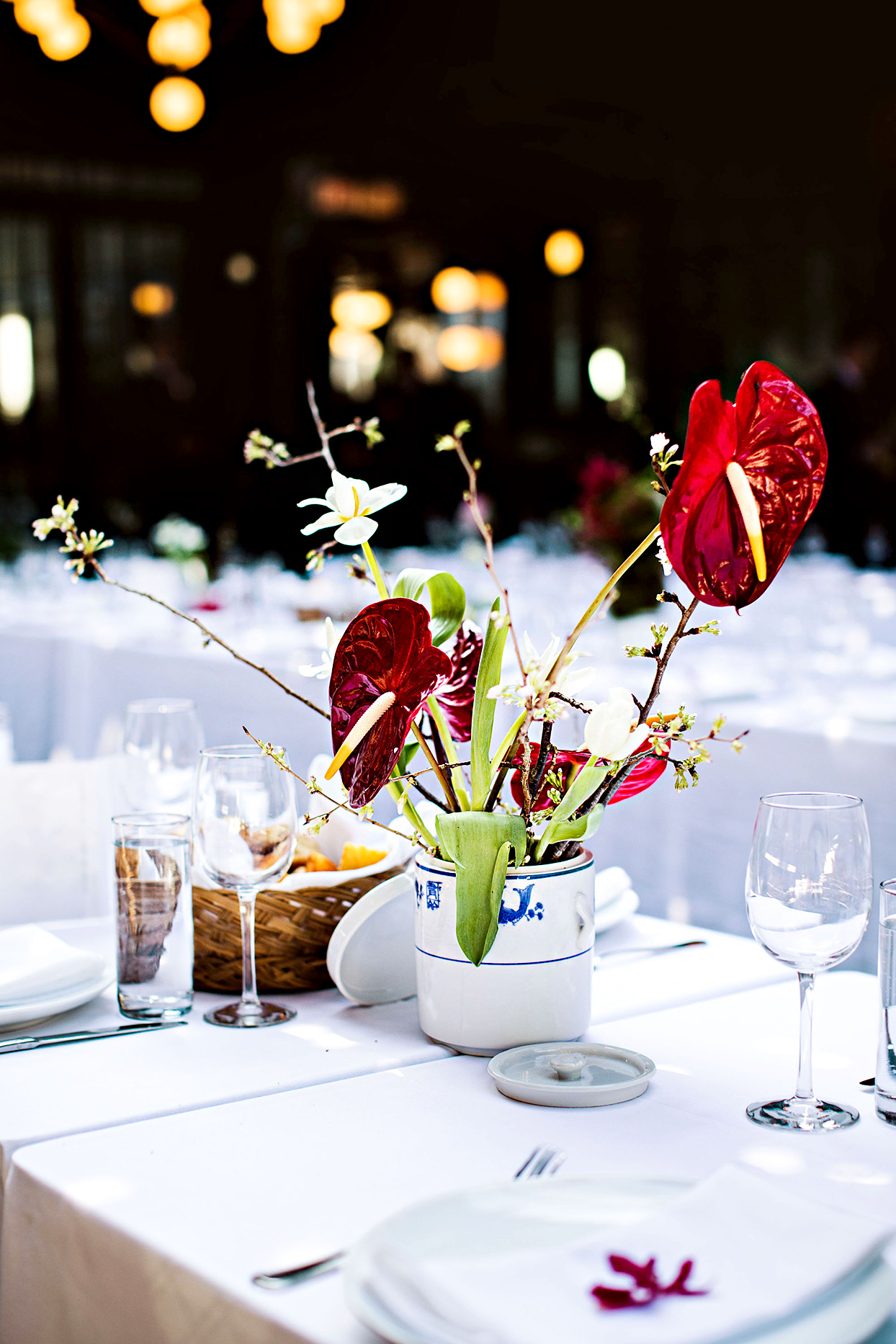 wedding centerpiece with 'Red Hearts' anthurium, white Dutch tulips, and cherry branches