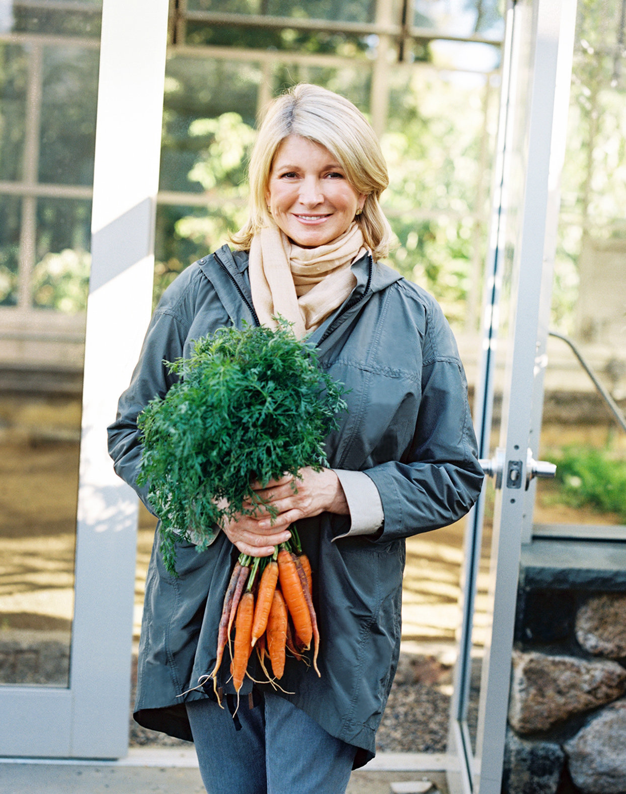Martha Stewart outside wearing blue jacket holding carrots