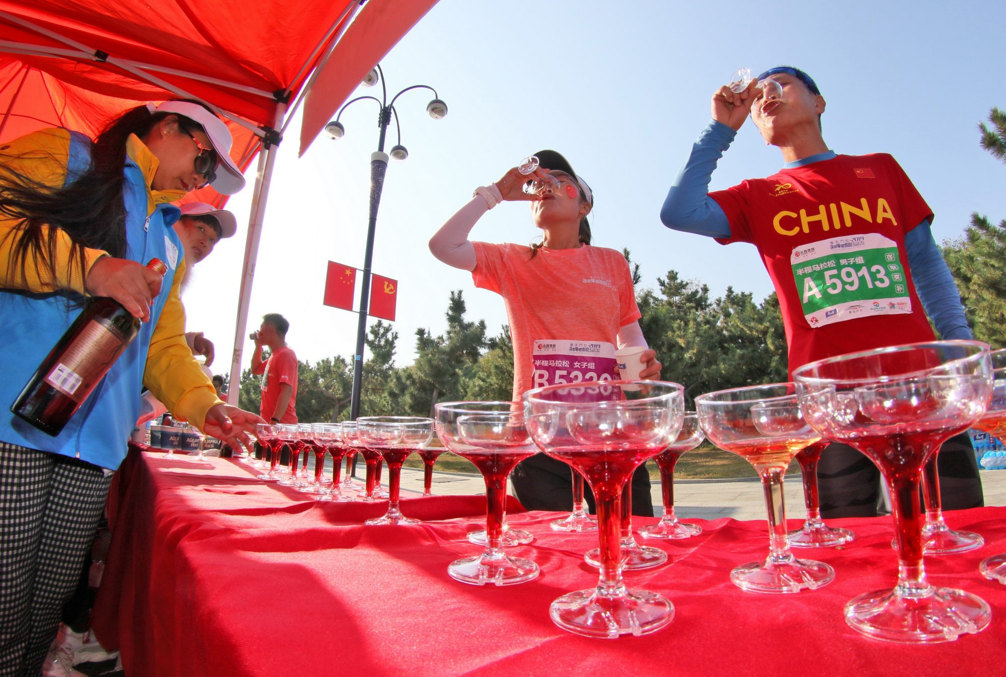runners stopping to drink wine during marathon