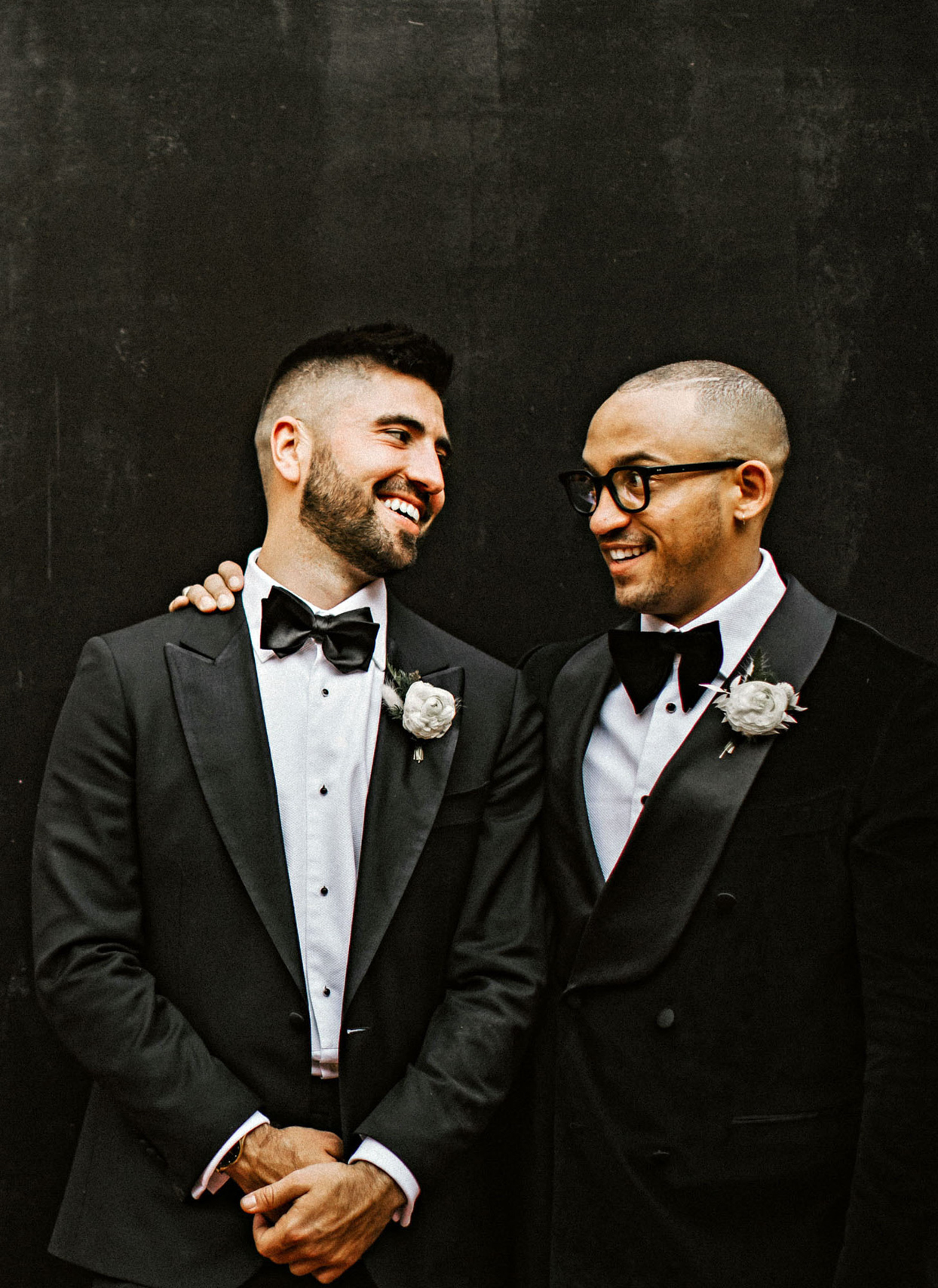 grooms in black suits smiling at each other for portrait