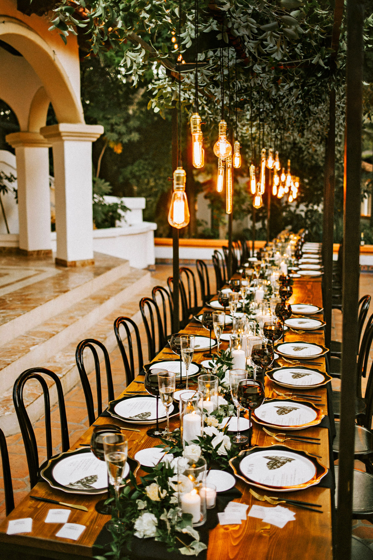 elegant wedding long table with black, green, and white decorations