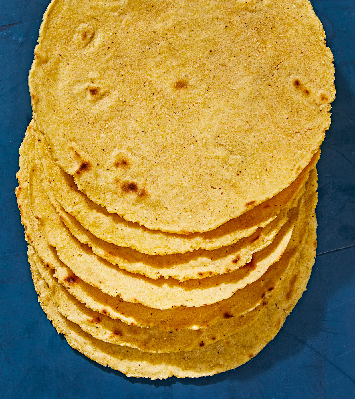 homemade corn tortillas stacked against blue background