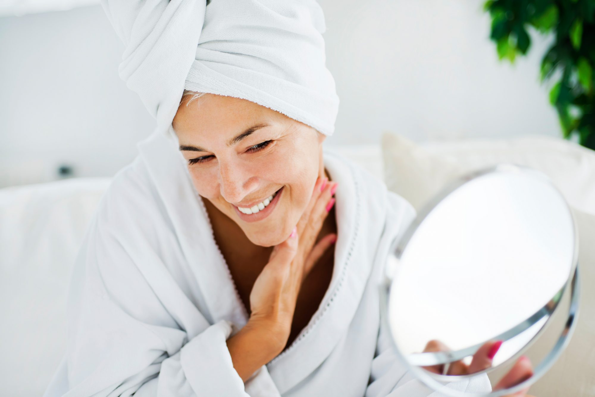 person wearing robe and hair in towel looking in mirror