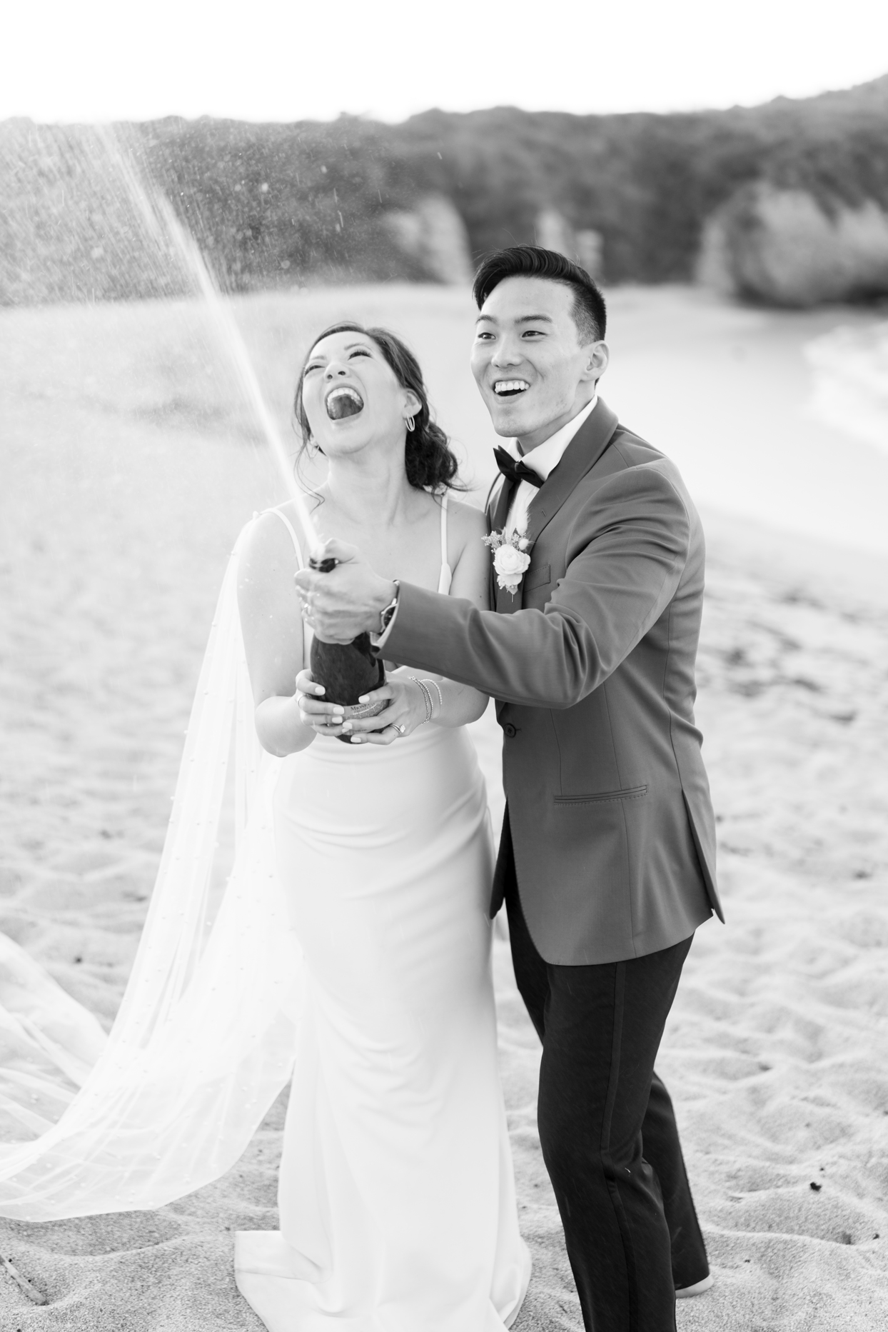bride and groom popping the champagne in the sand