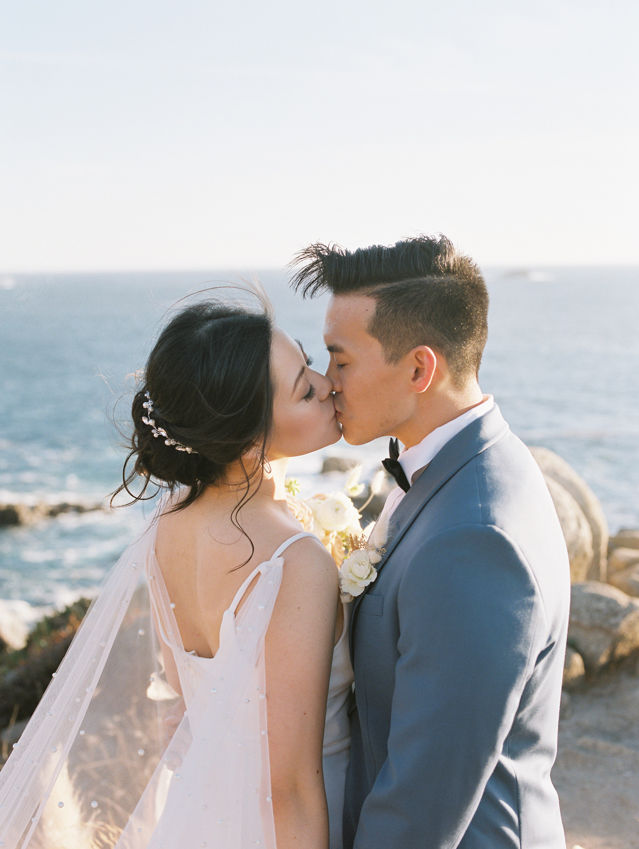 bride and groom kissing on cliffside